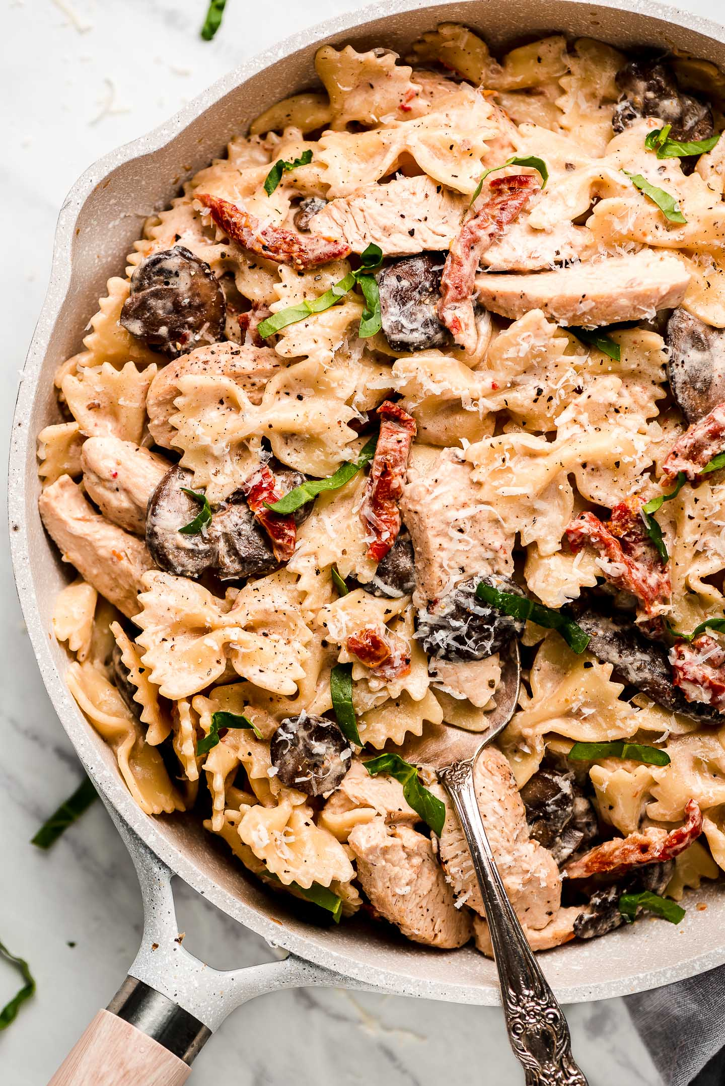 Macaroni Grill's copycat Chicken Pasta Milano in a skillet garnished with basil and shredded Parmesan cheese.