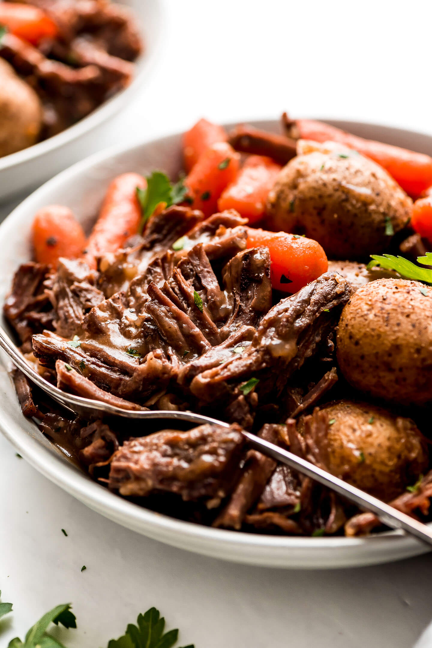 Pot Roast in a bowl with potatoes, and carrots, and drizzled with brown gravy.