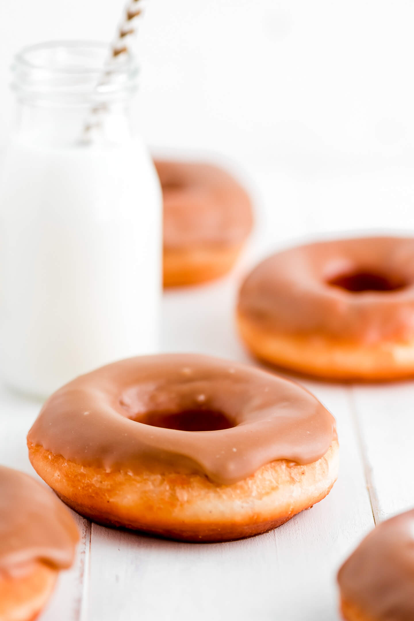 A few donuts with maple glaze on a table with a bottle of milk.