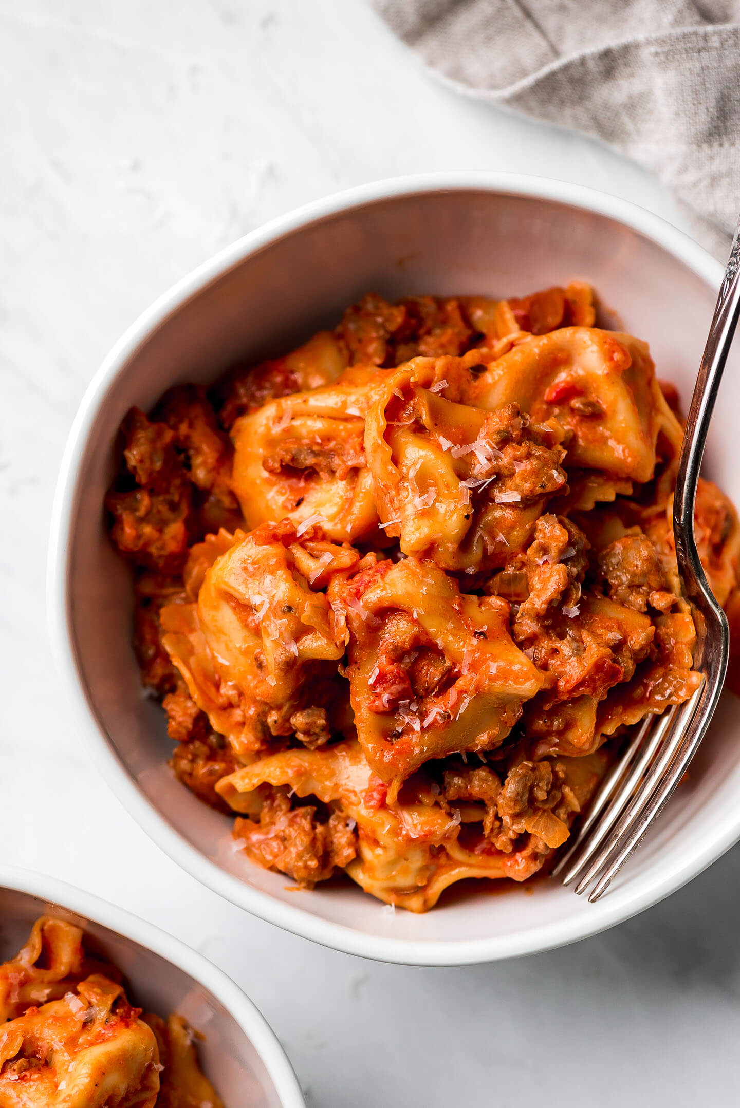 A bowl of tortellini in creamy sausage red sauce and a fork in the side