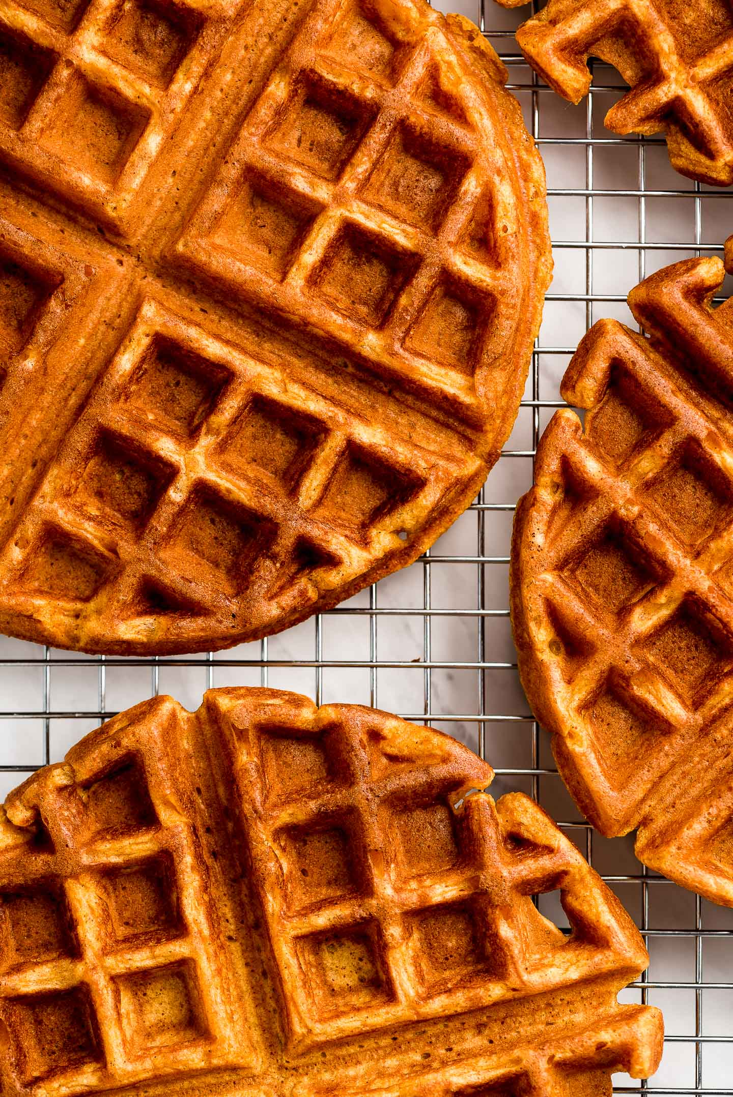 Pumpkin waffles on a wire cooling rack.
