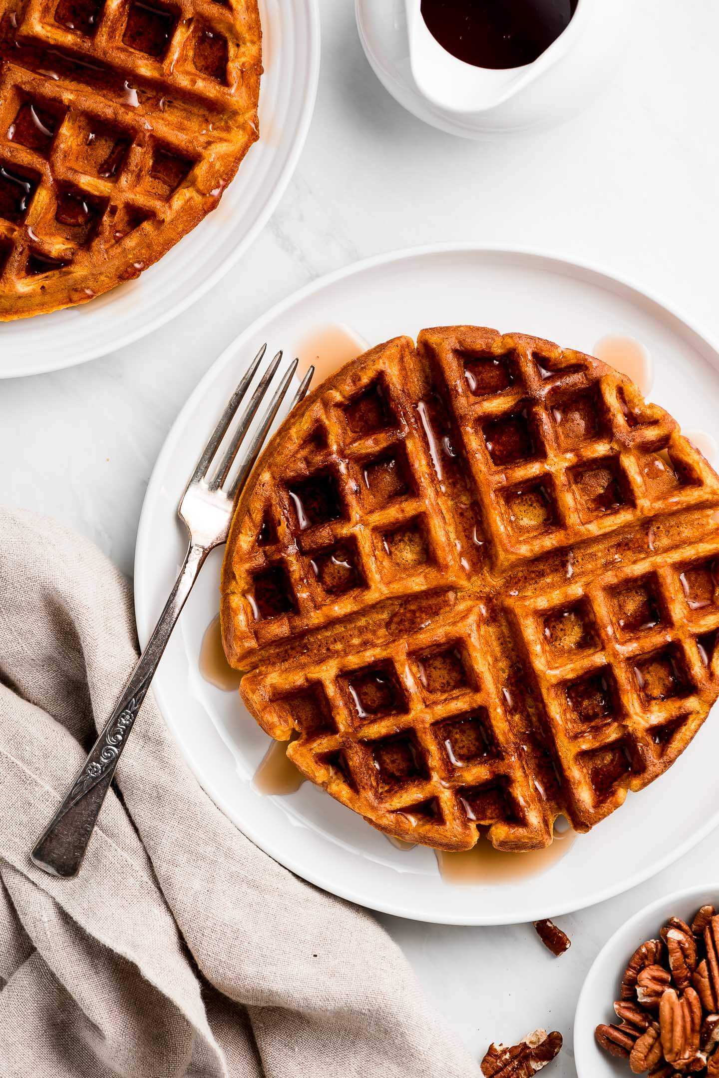 A simple pumpkin waffle on a plate with a fork and syrup drizzled over the top.