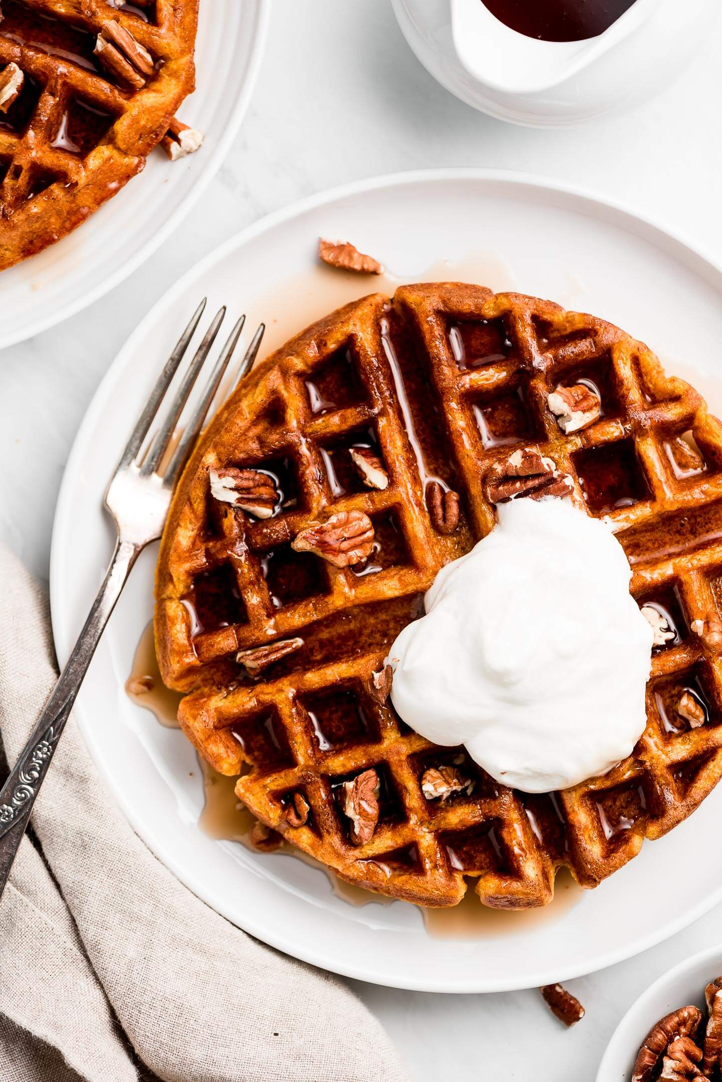 Pumpkin waffle on a white plate with maple syrup, pecans, and whipped cream on top.