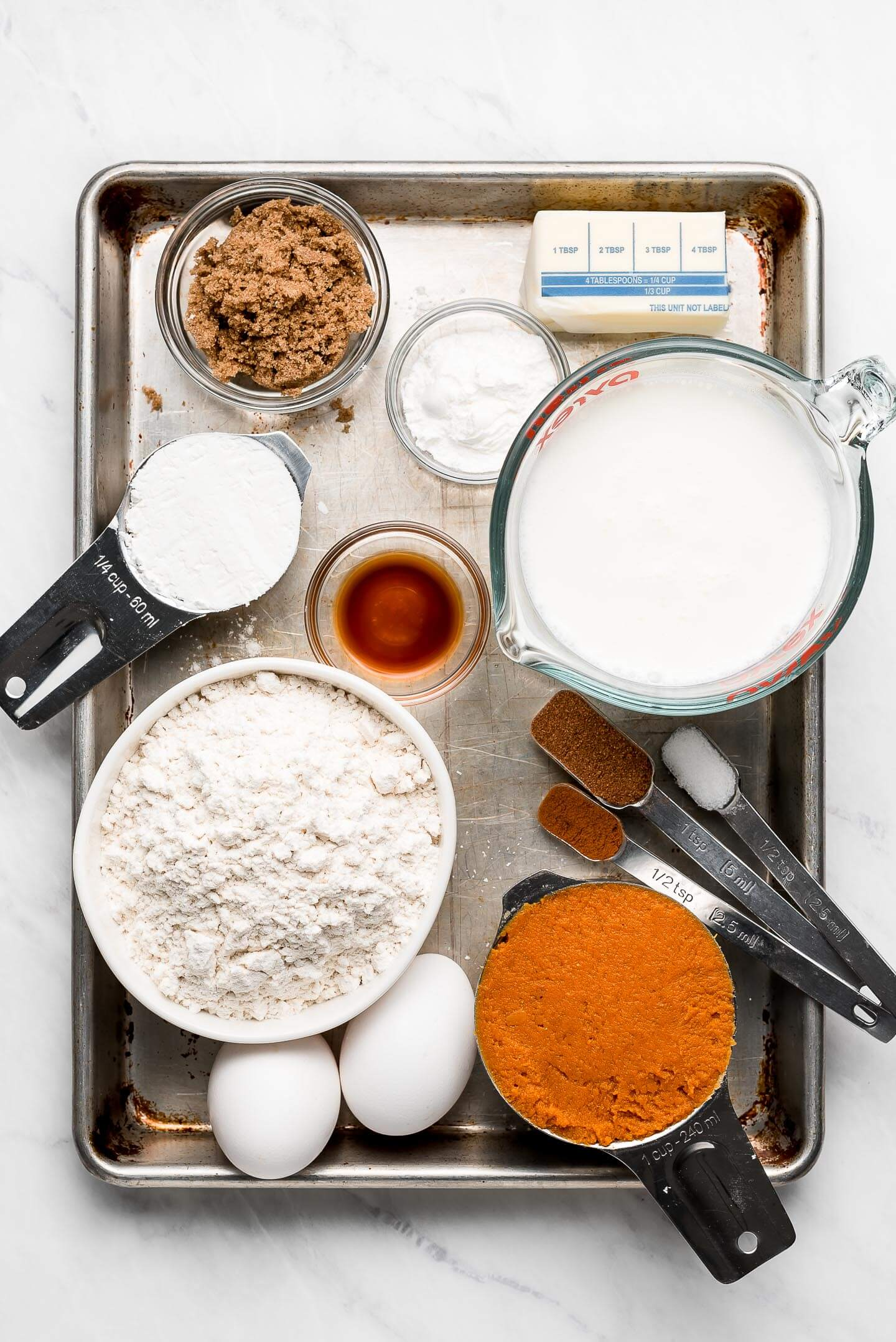 Ingredients (brown sugar, milk, flour, eggs, butter, vanilla, spices) on a baking sheet.