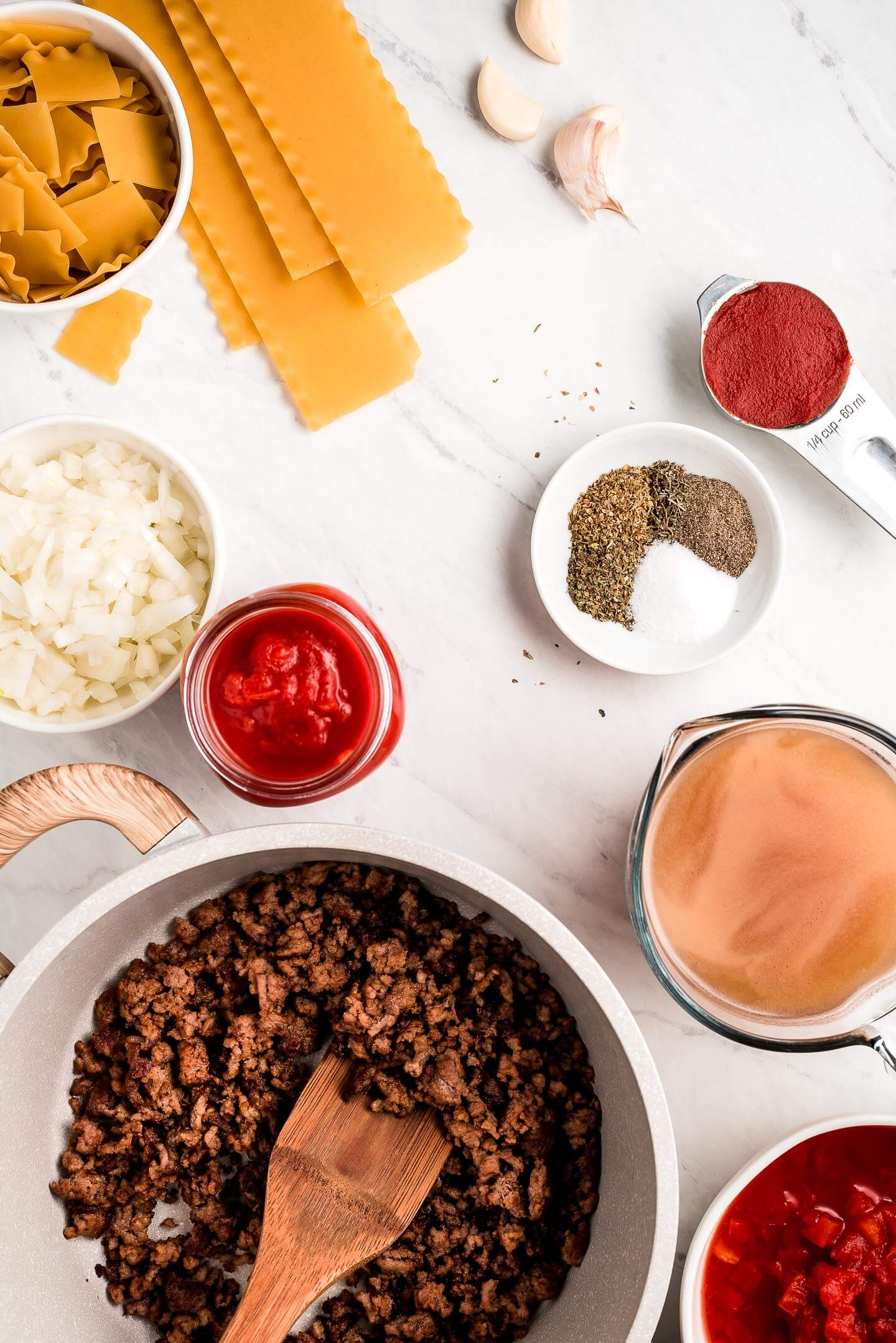 Ingredients on a marble surface- browned ground beef, lasagna noodles, onions, tomatoes, broth, garlic, spices.