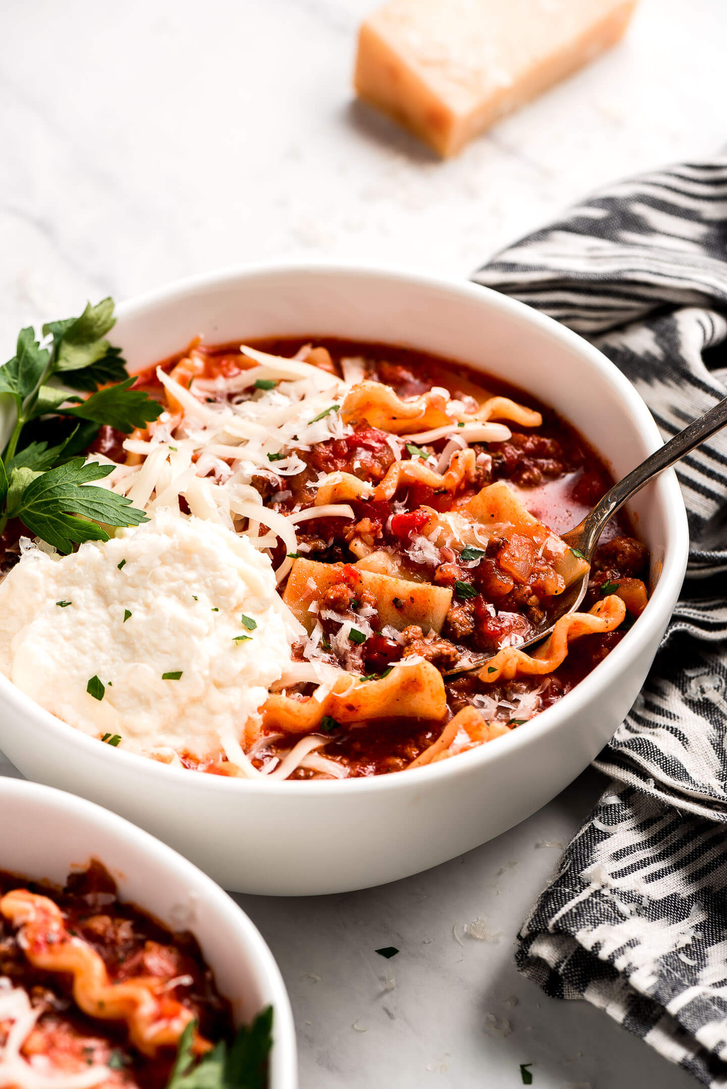 A bowl of Lasagna Soup and a spoon lifting a bite out.