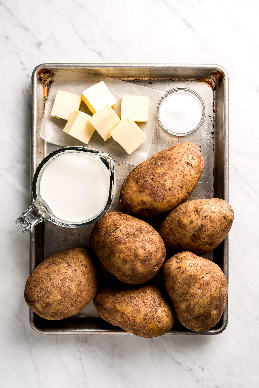 A sheet pan with russet potatoes, milk, salt, and butter.