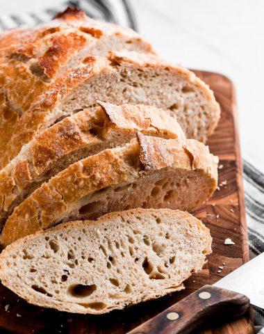 No Knead Bread sliced on a cutting board.