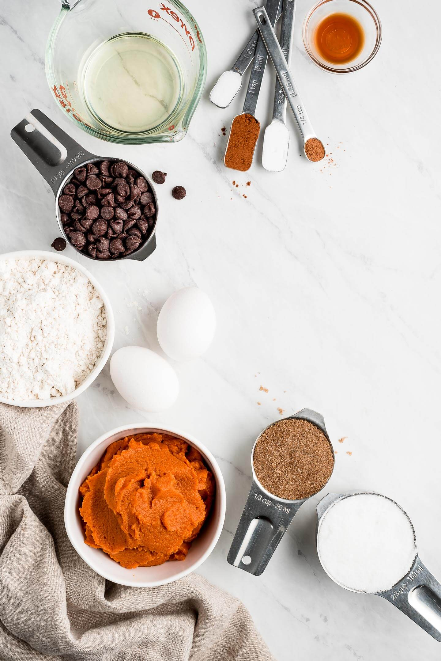 Shot of ingredients on a marble surface- flour, pumpkin pure, eggs, oil, chocolate chips, sugar, spices, and vanilla.