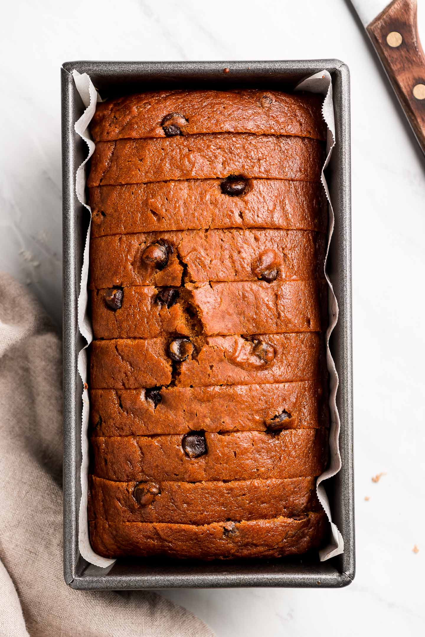 Chocolate Chip Pumpkin Bread sliced and in a loaf pan.