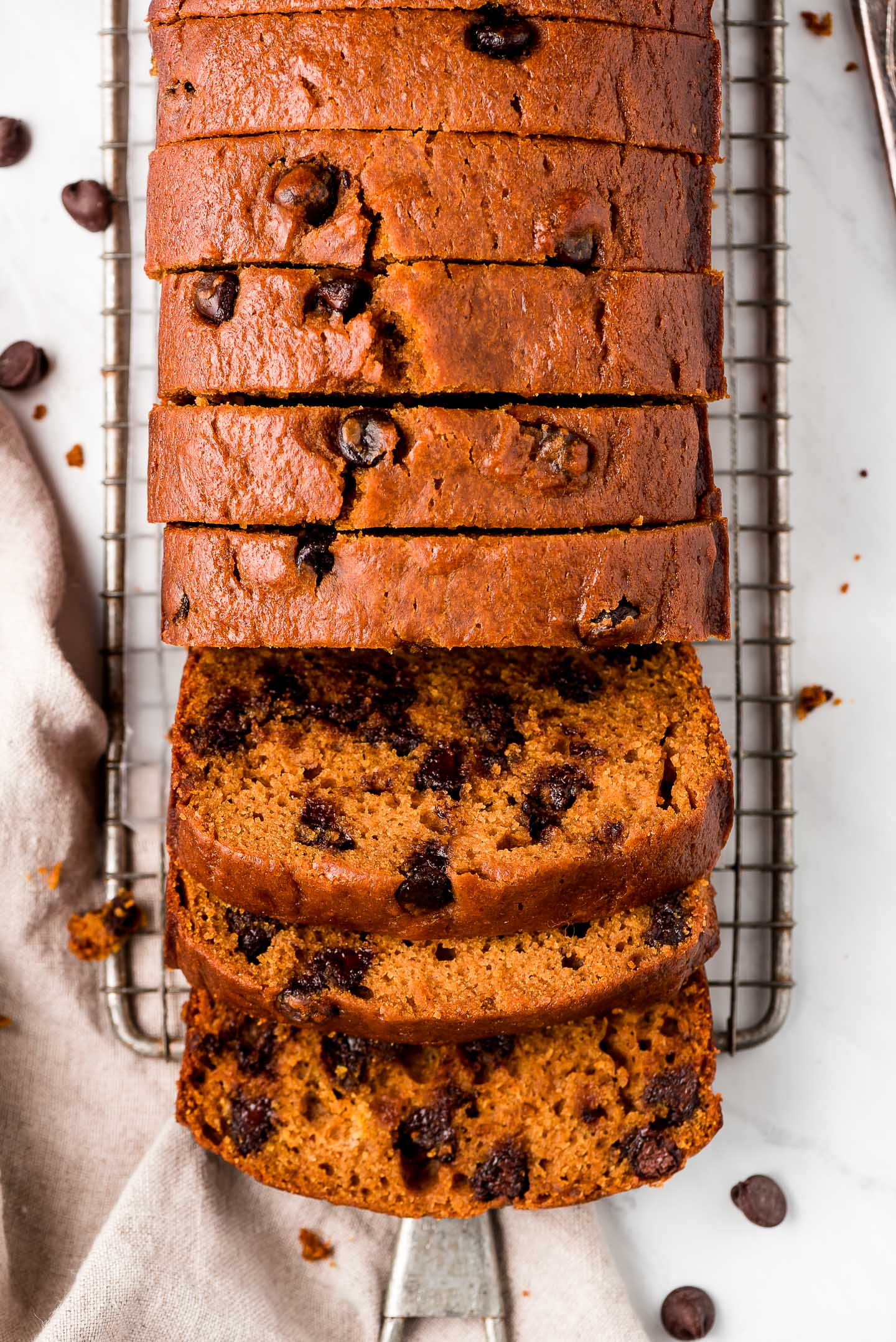 A loaf of sliced pumpkin chocolate chip bread on a cooling rack with slices falling forward.
