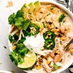 White Chicken Chili in a bowl topped with avocado slices, cilantro, jalapeno, chips, cheese, sour cream, and a lime.