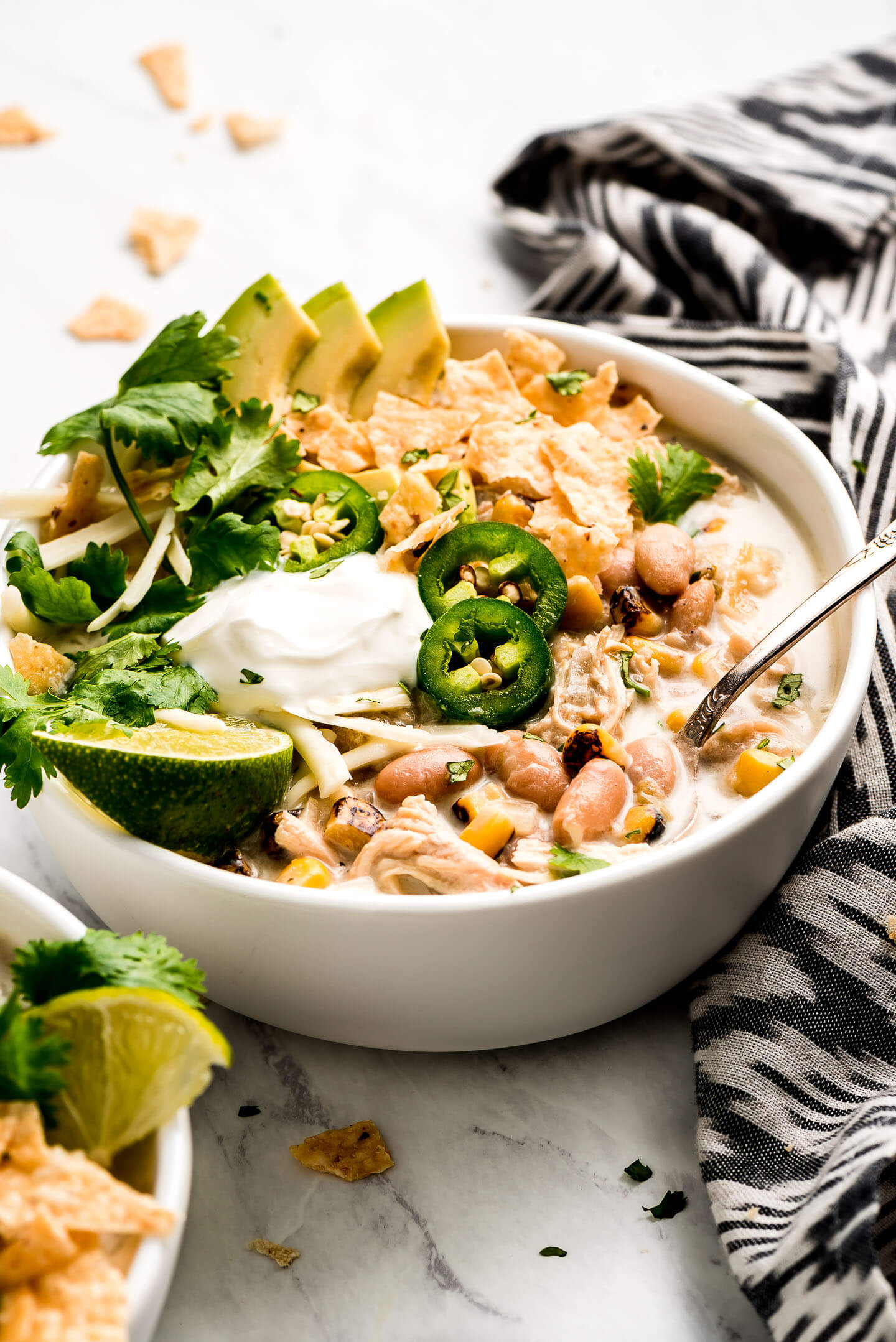 Angled shot of a bowl of creamy white chicken chili loaded with toppings.