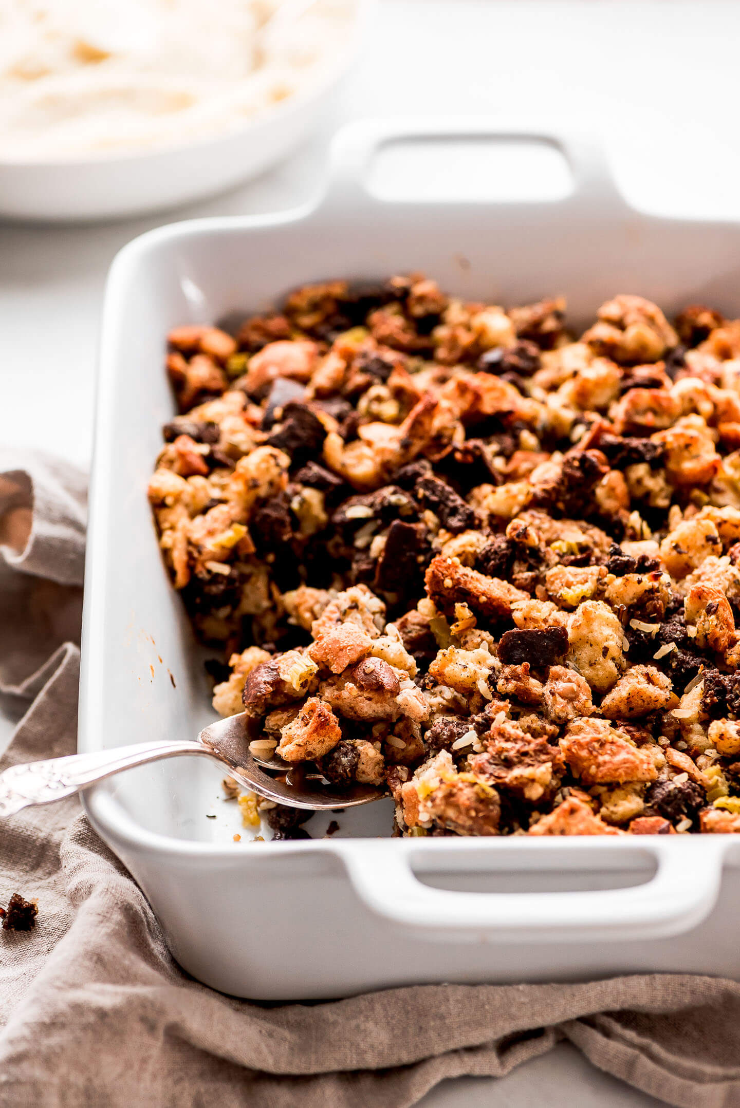 Scooping a spoonful of Turkey Stuffing out of a casserole dish.