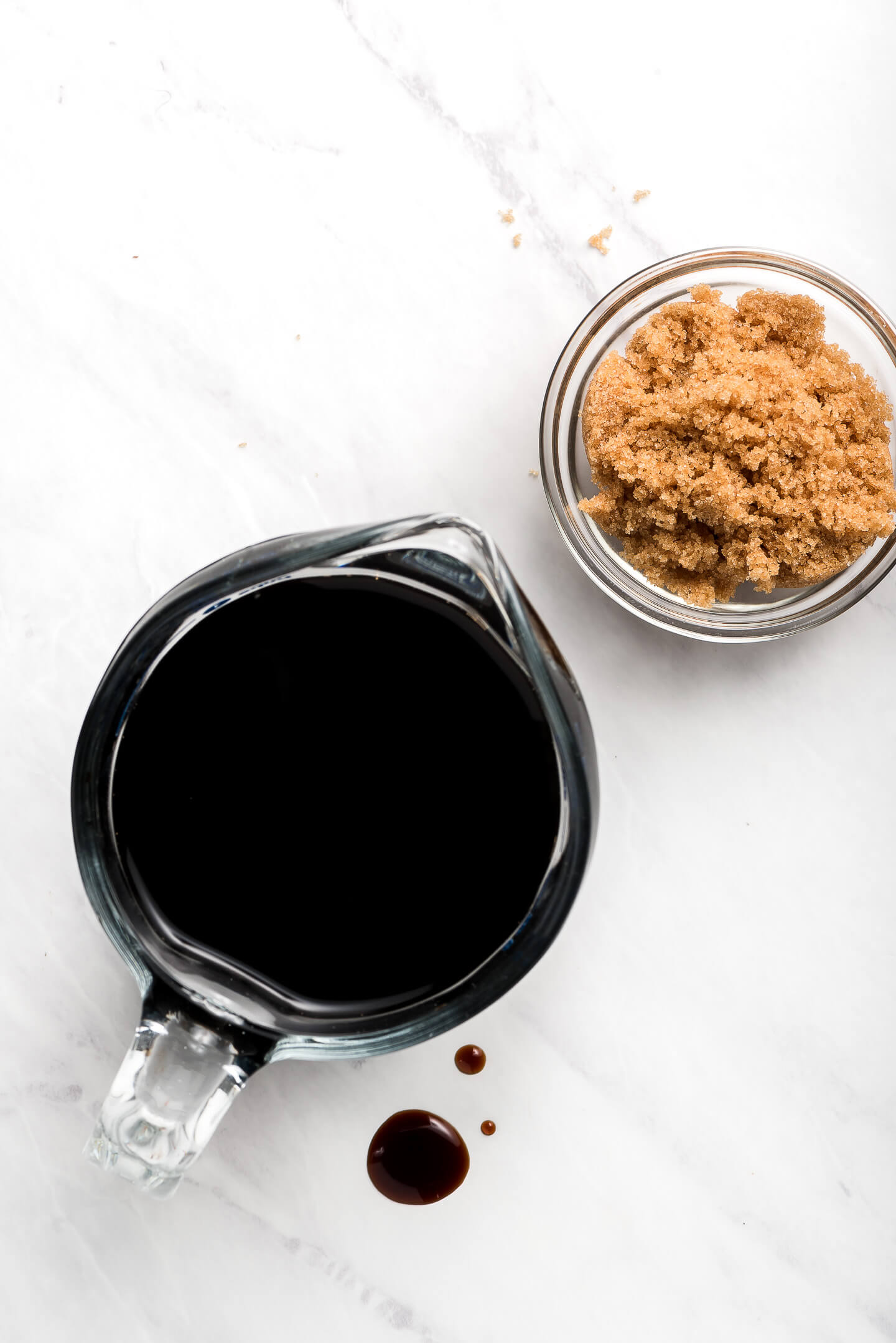 A glass measuring cup of balsamic vinegar and a small dish of brown sugar.