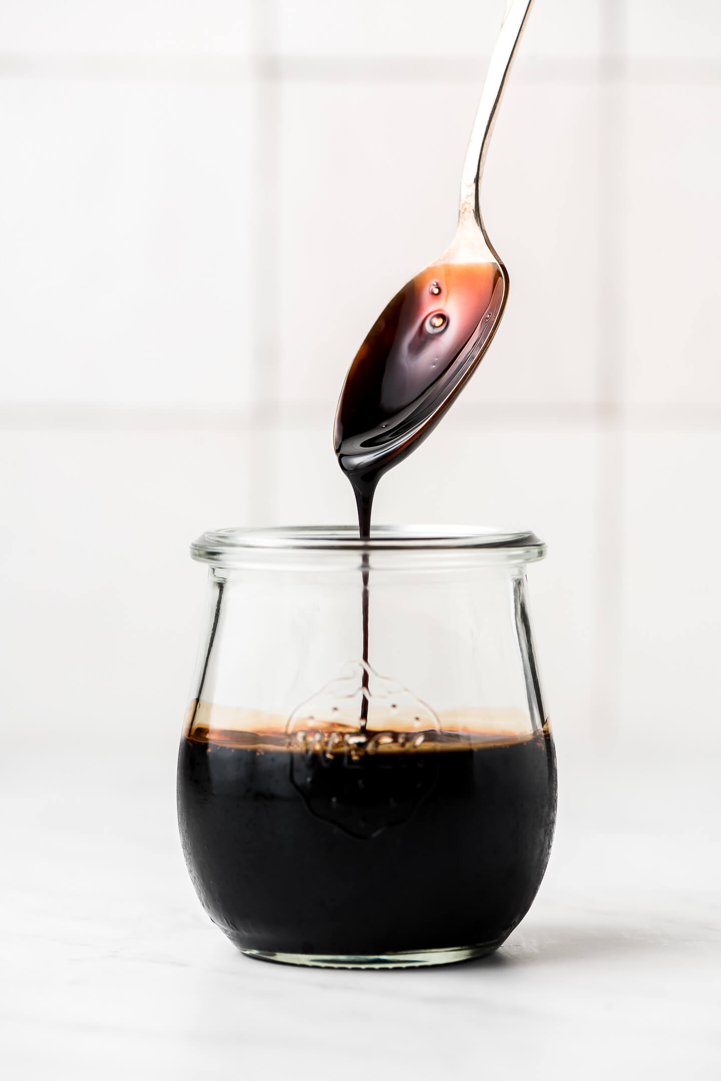Lifting a spoon out of a jar and letting Balsamic Glaze drip back down into it.