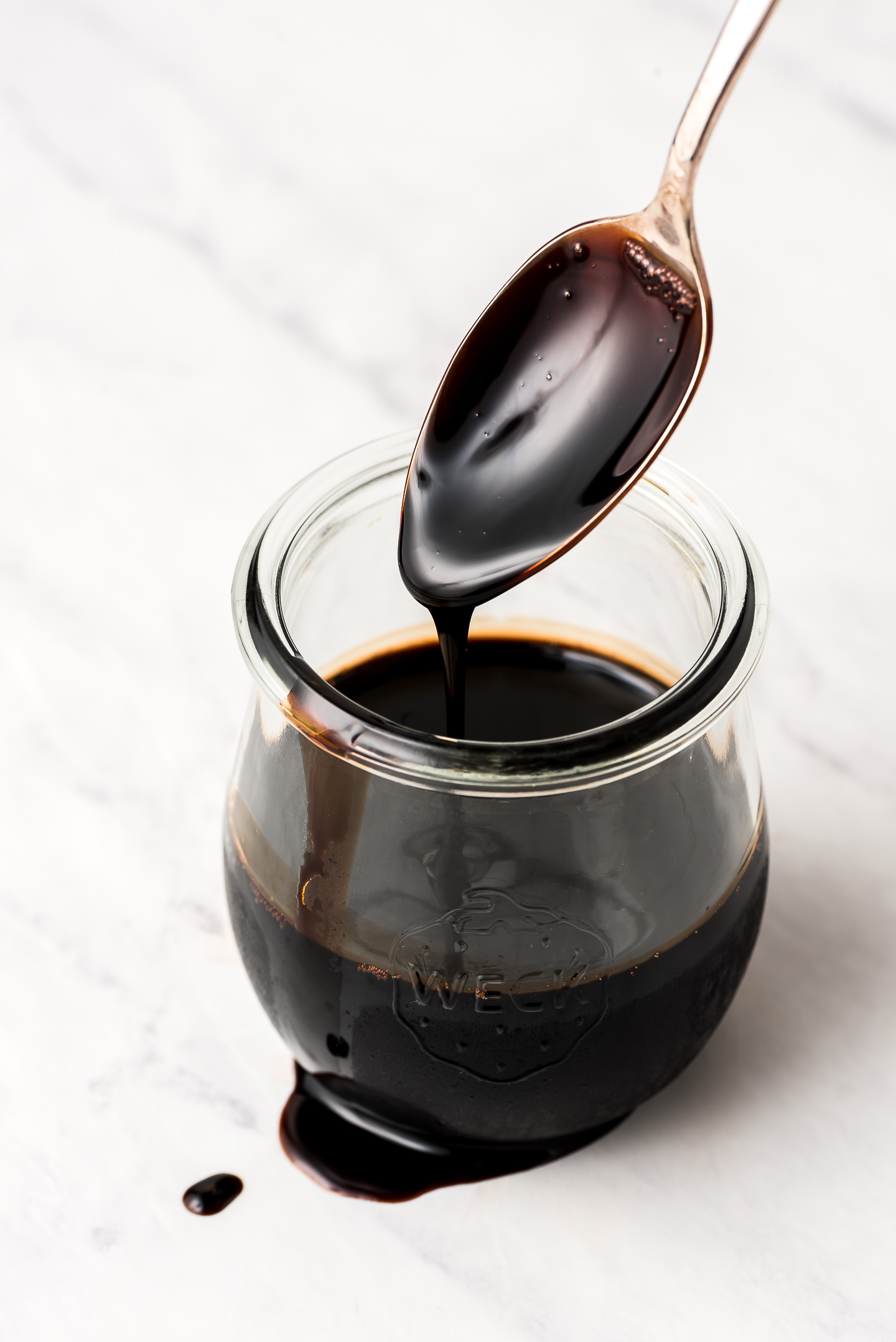 Lifting a spoon coated with Balsamic Glaze out of a Weck jar.