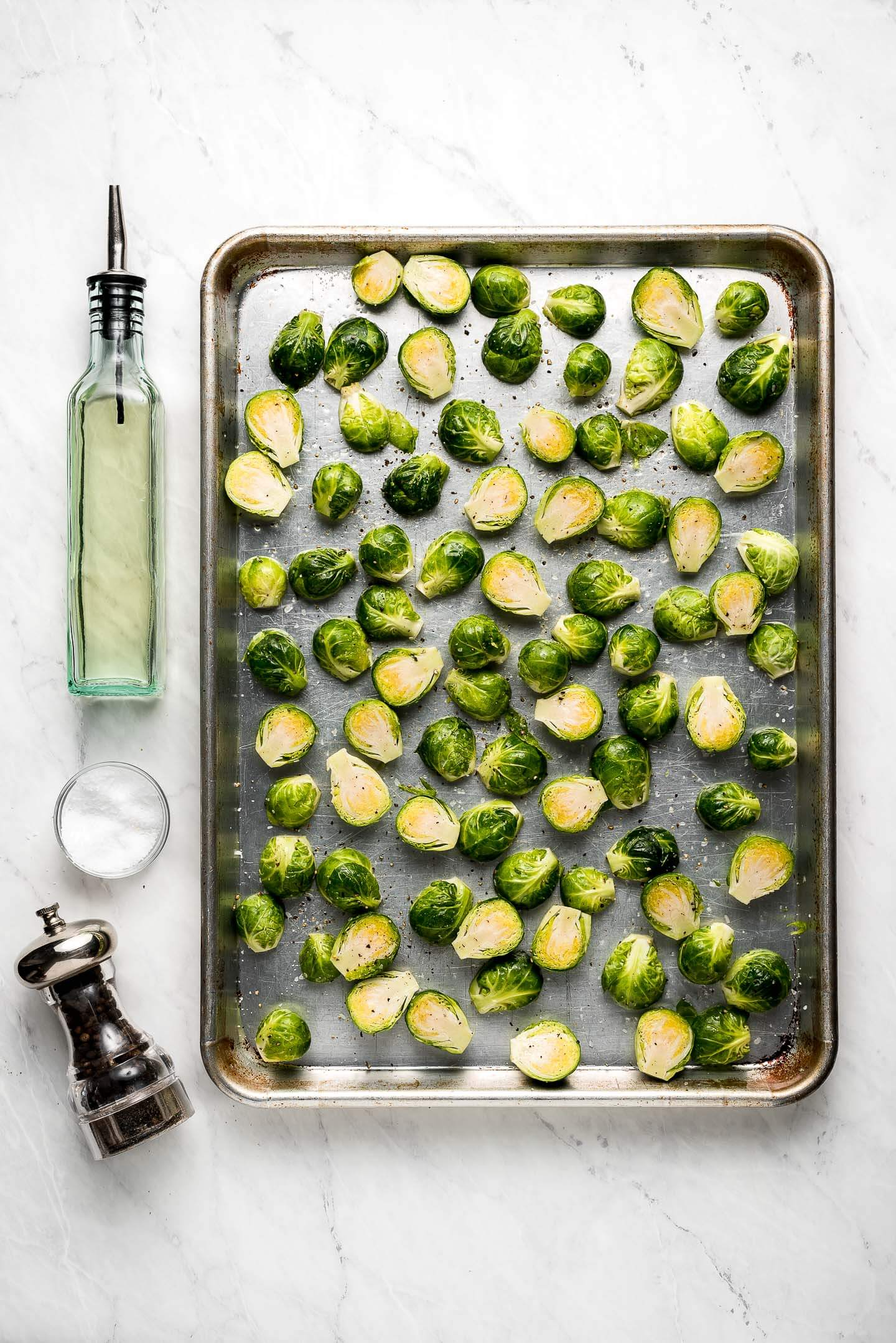 Raw brussels sprouts drizzled with oil on a baking sheet.