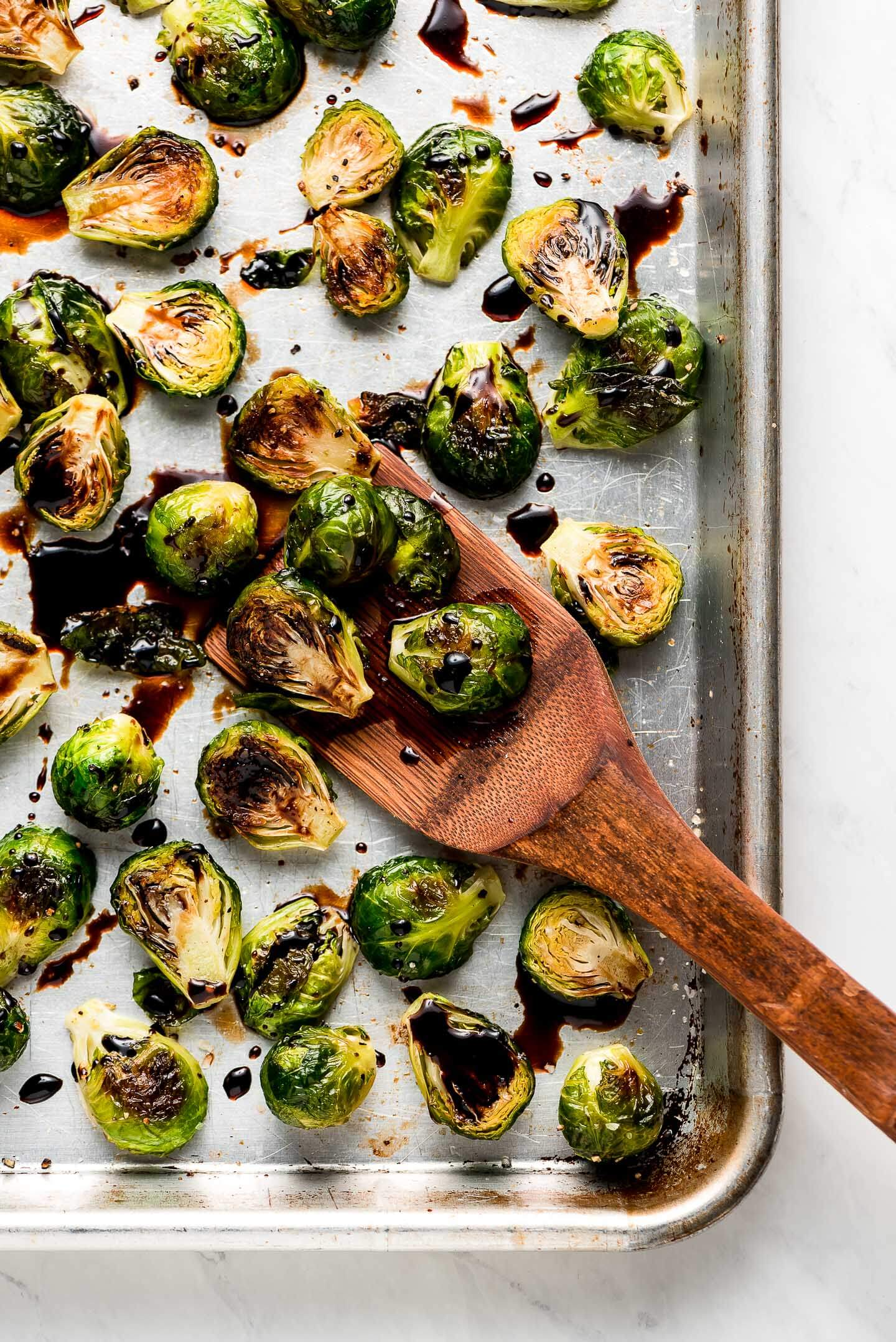 Roasted Brussel Sprouts on a baking sheet drizzled with balsamic reduction.