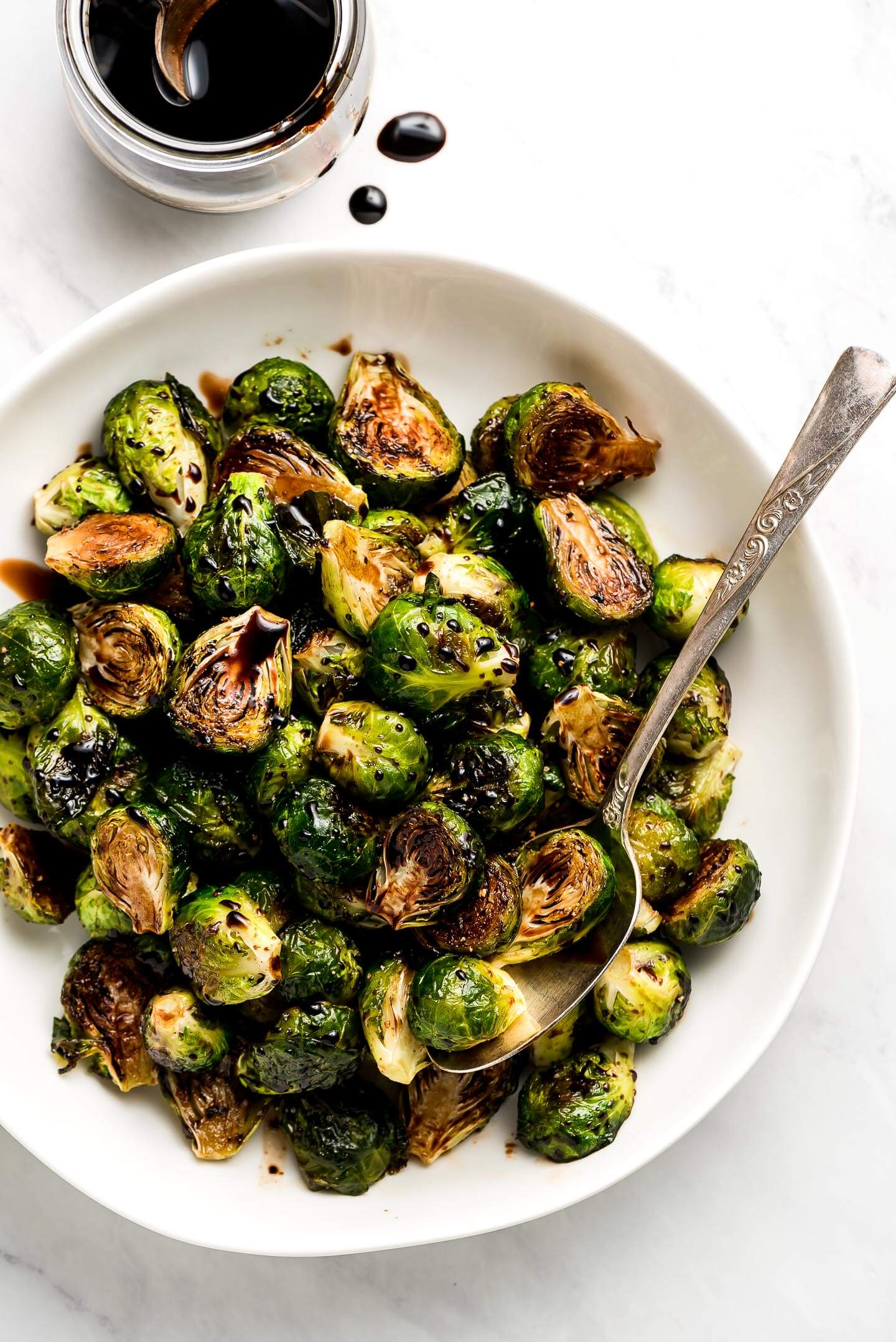 A serving bowl of Roasted Brussel Sprouts with Balsamic Glaze.