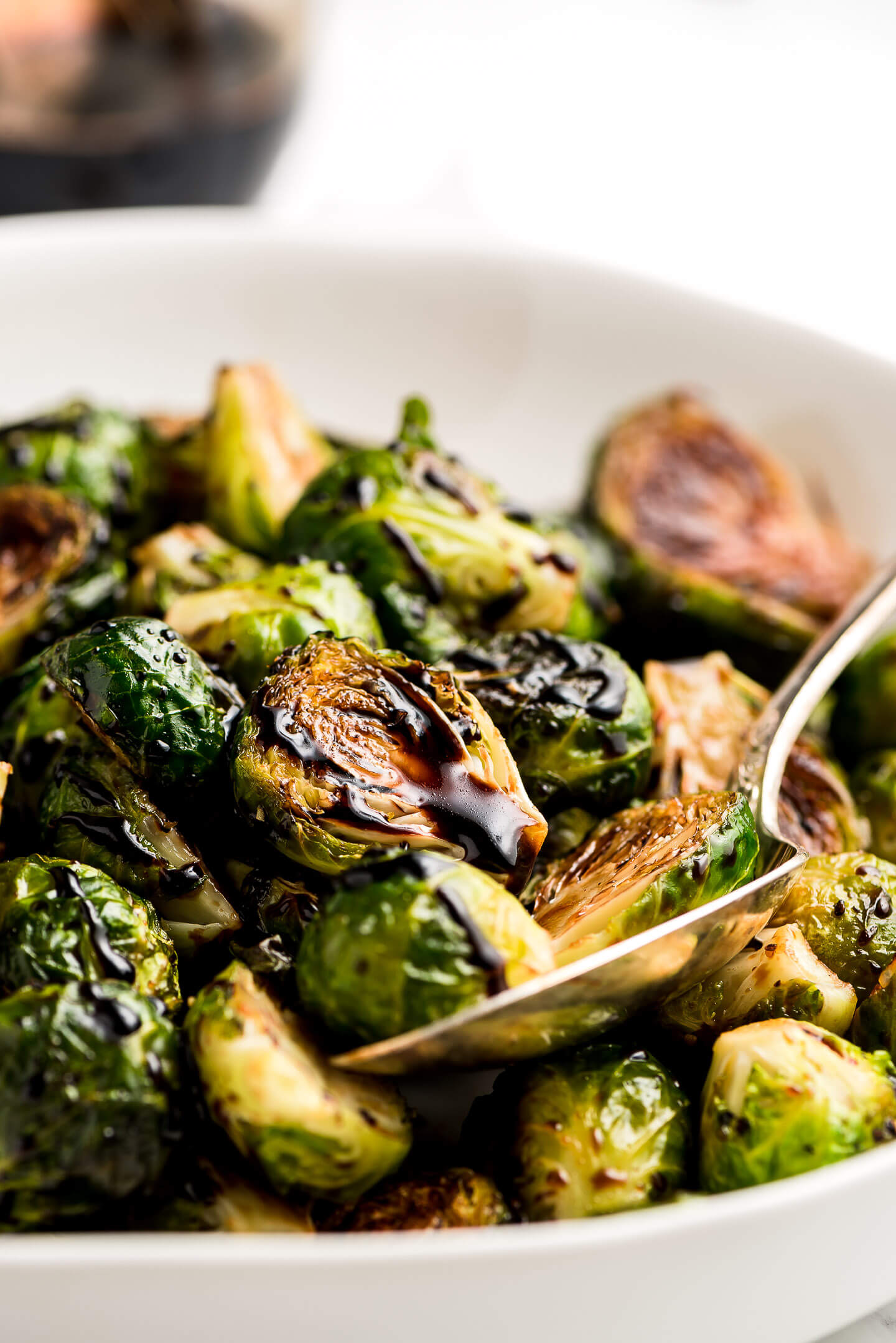 Balsamic Brussel Sprouts in a serving bowl with a spoon.