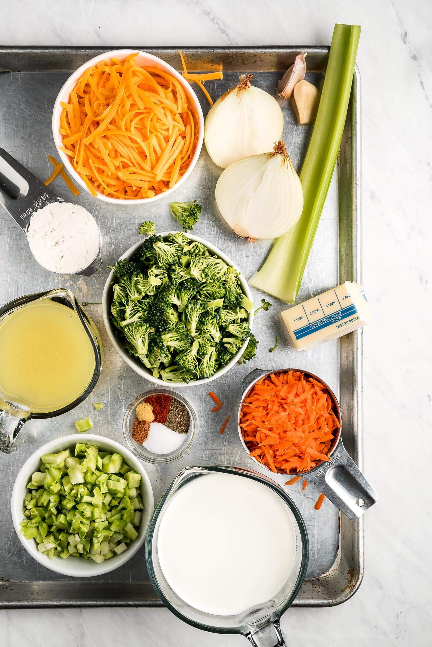 A baking sheet with ingredients on it- shredded cheese, broccoli florets, shredded carrots, celery, cream, spices, onions, flour, butter, and broth.