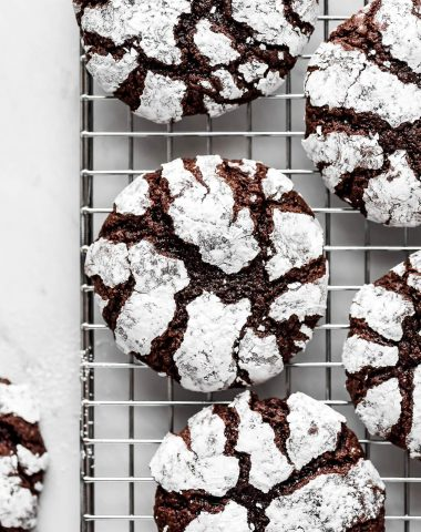 Brownie cookies with powdered sugar on cooling rack.