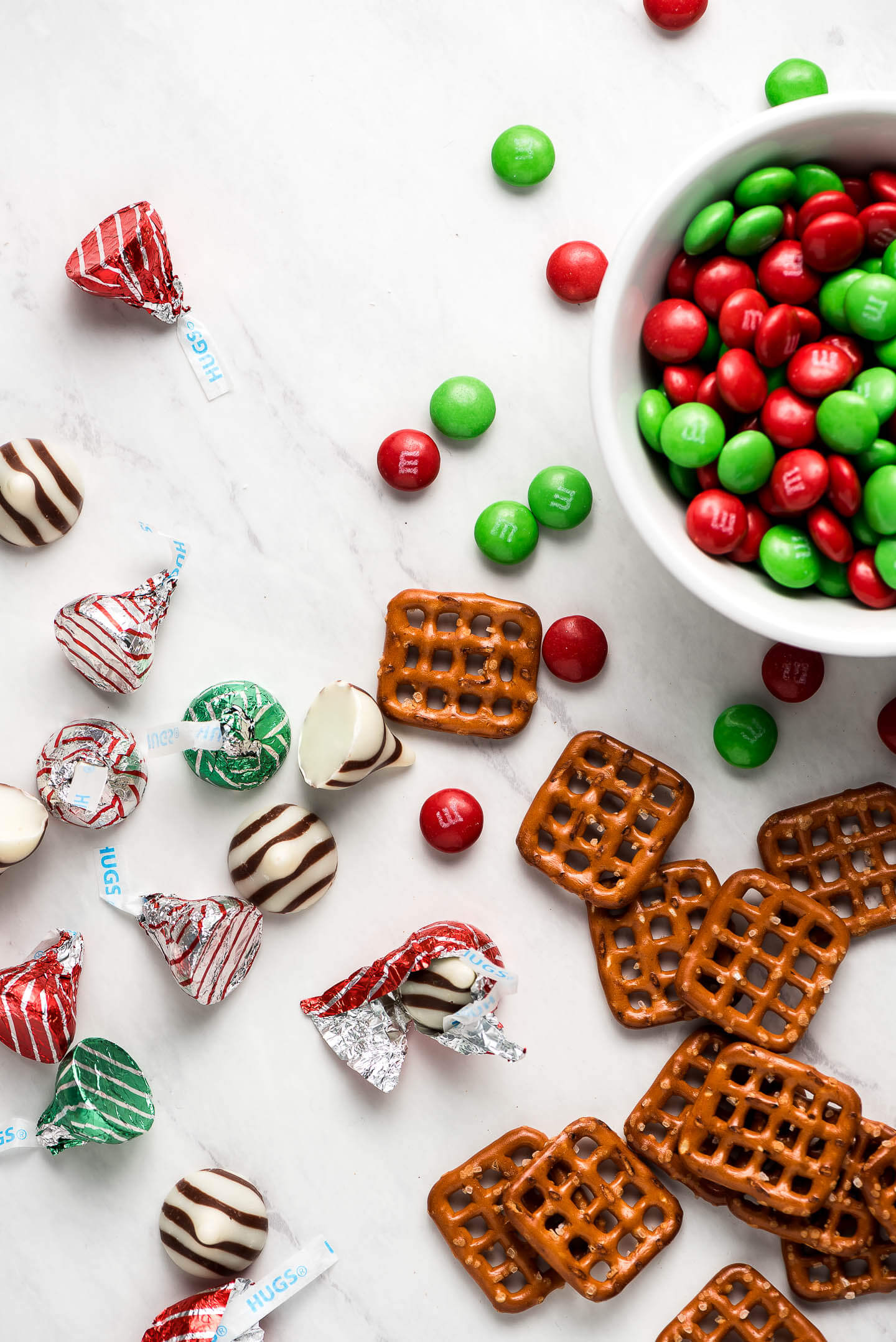 Snap pretzels, Hershe's Hugs, and red & green M&M's on a marble surface.
