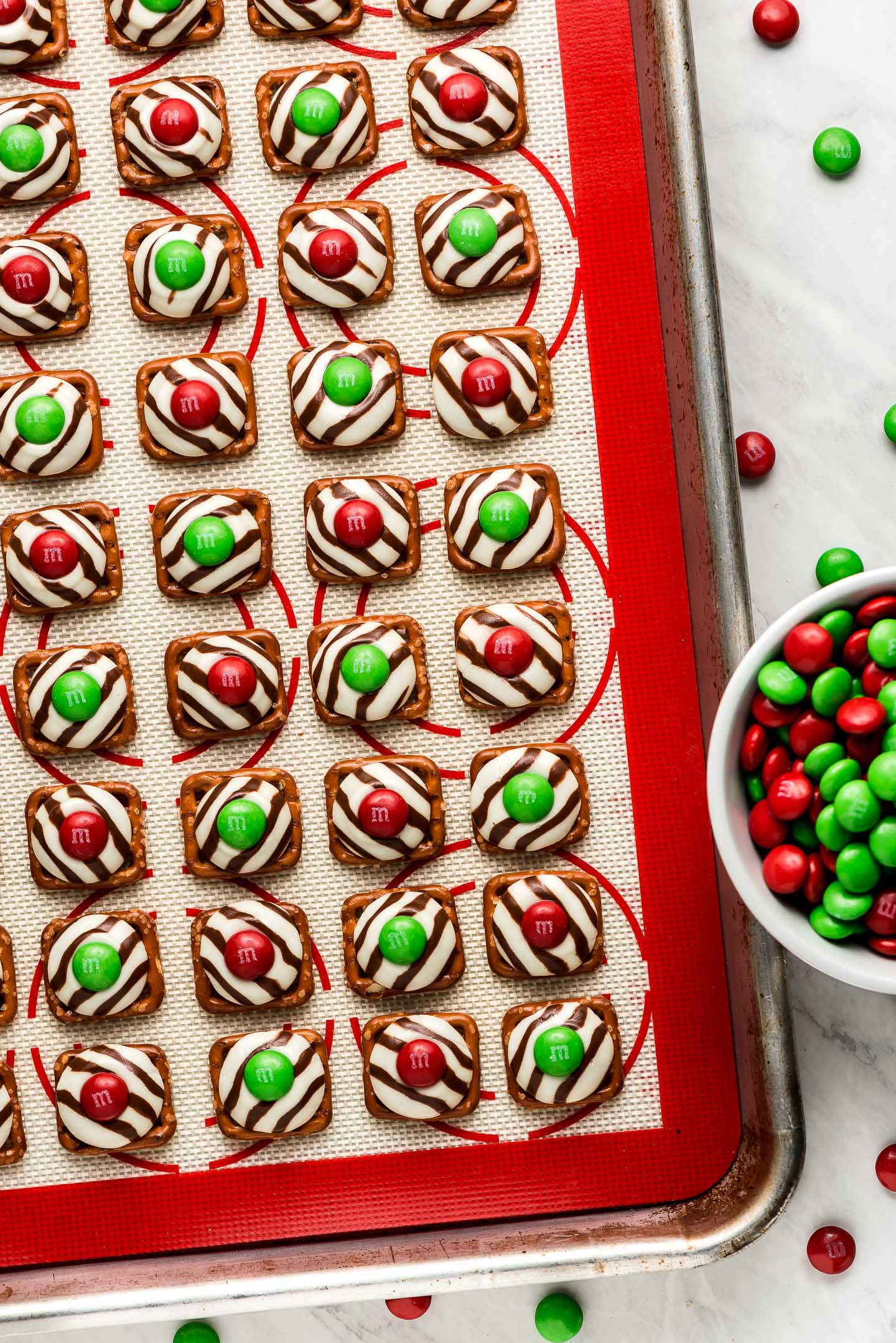Christmas Pretzel Hugs on a silicone lined baking sheet with M&M's on the side.