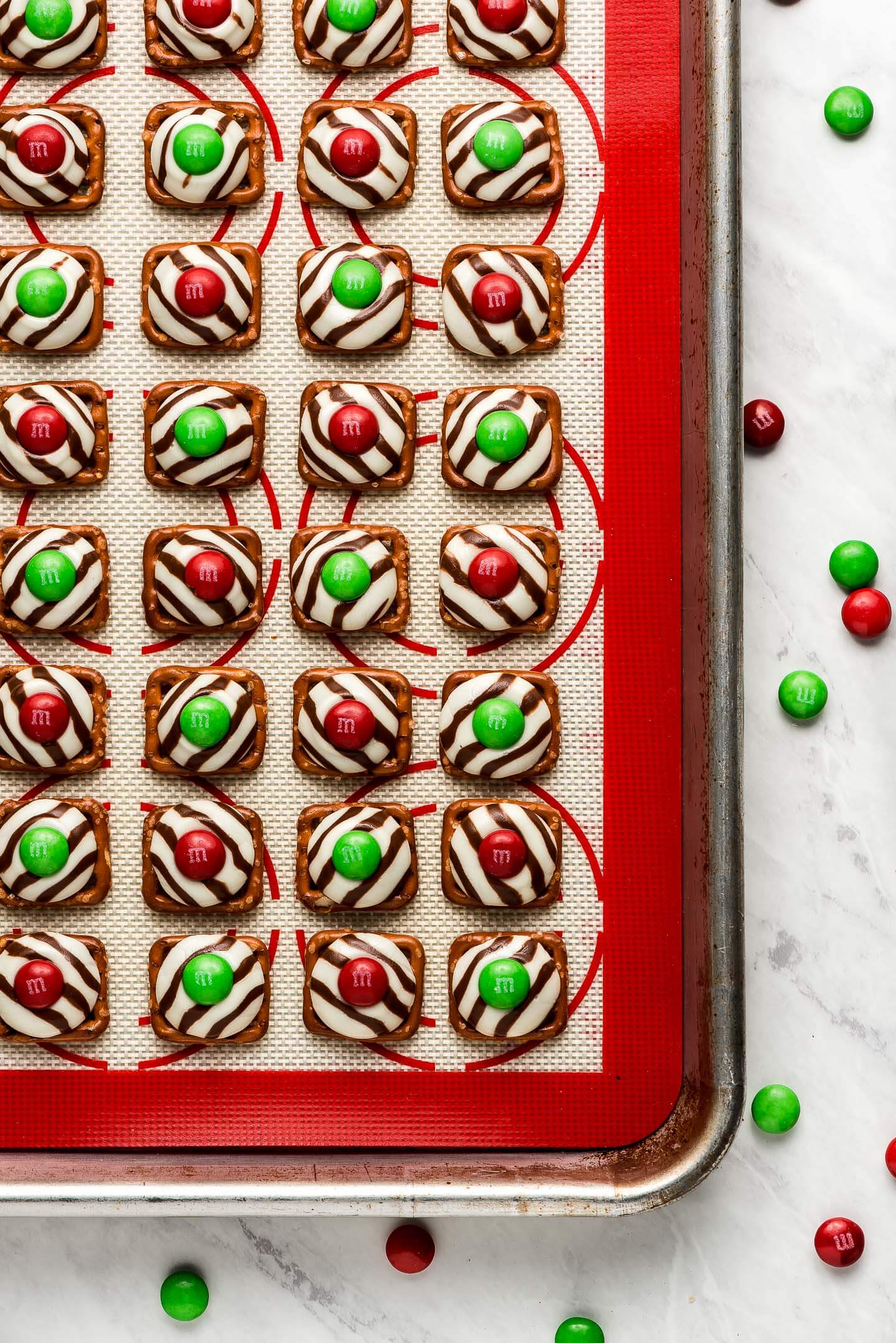 A baking sheet lined with a red silicone mat topped with Christmas Pretzel M&M Hugs.