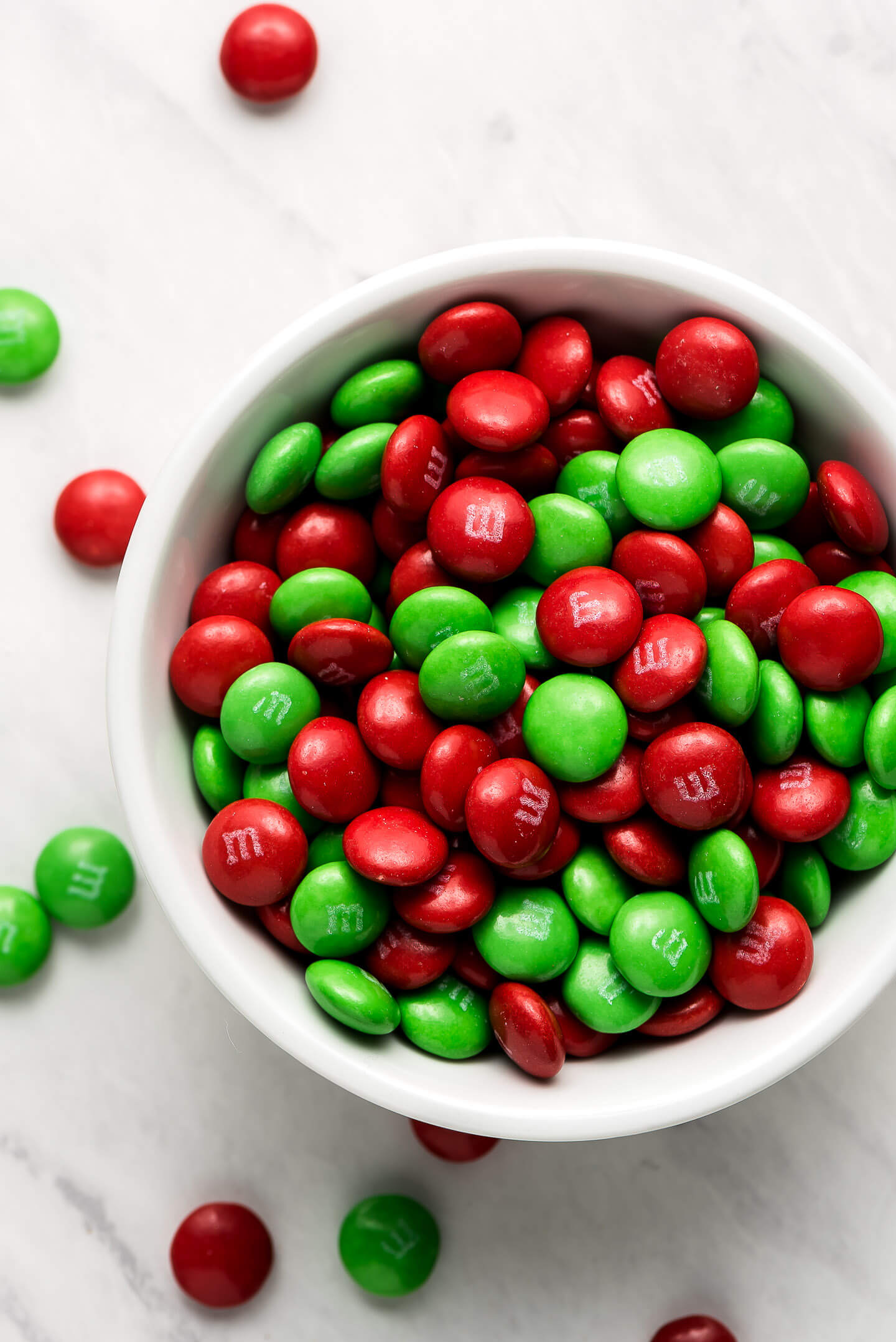 A close up of red and green Christmas M&M's in a bowl.