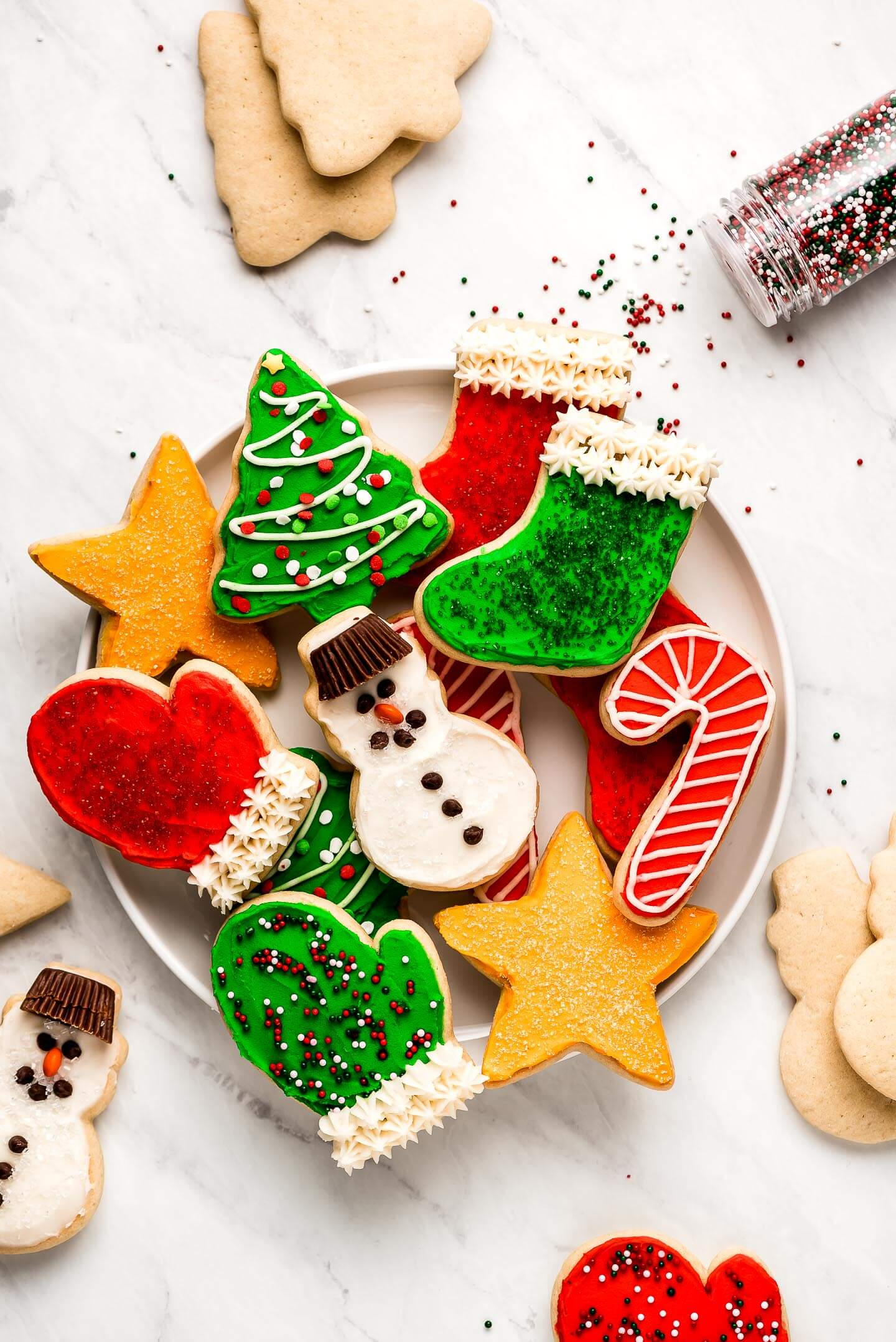 Christmas Sugar Cookies on a white plate with cookies and sprinkles surrounding.
