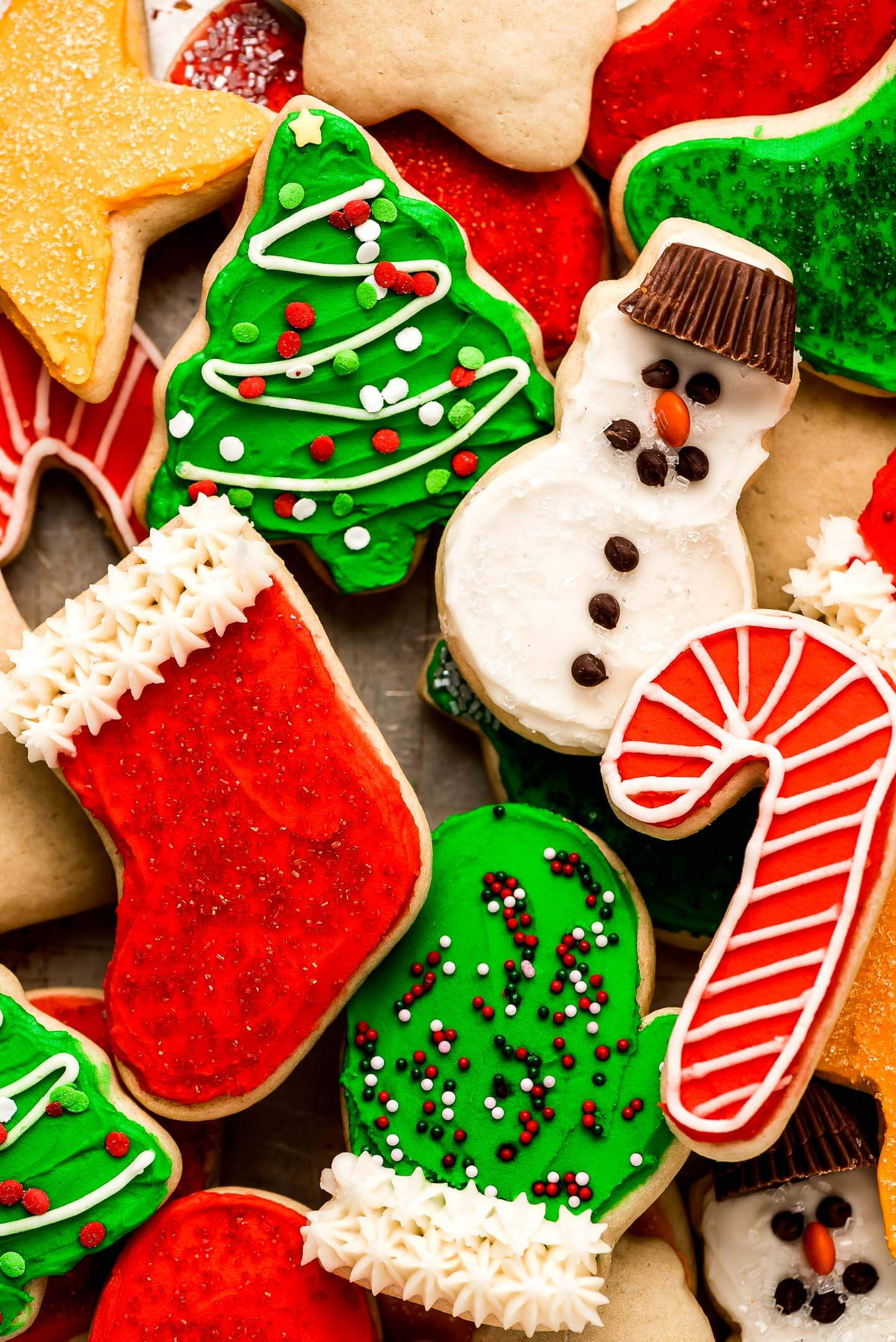 A close up of Christmas cut-out sugar cookies decorated with sprinkles and chocolate chips.