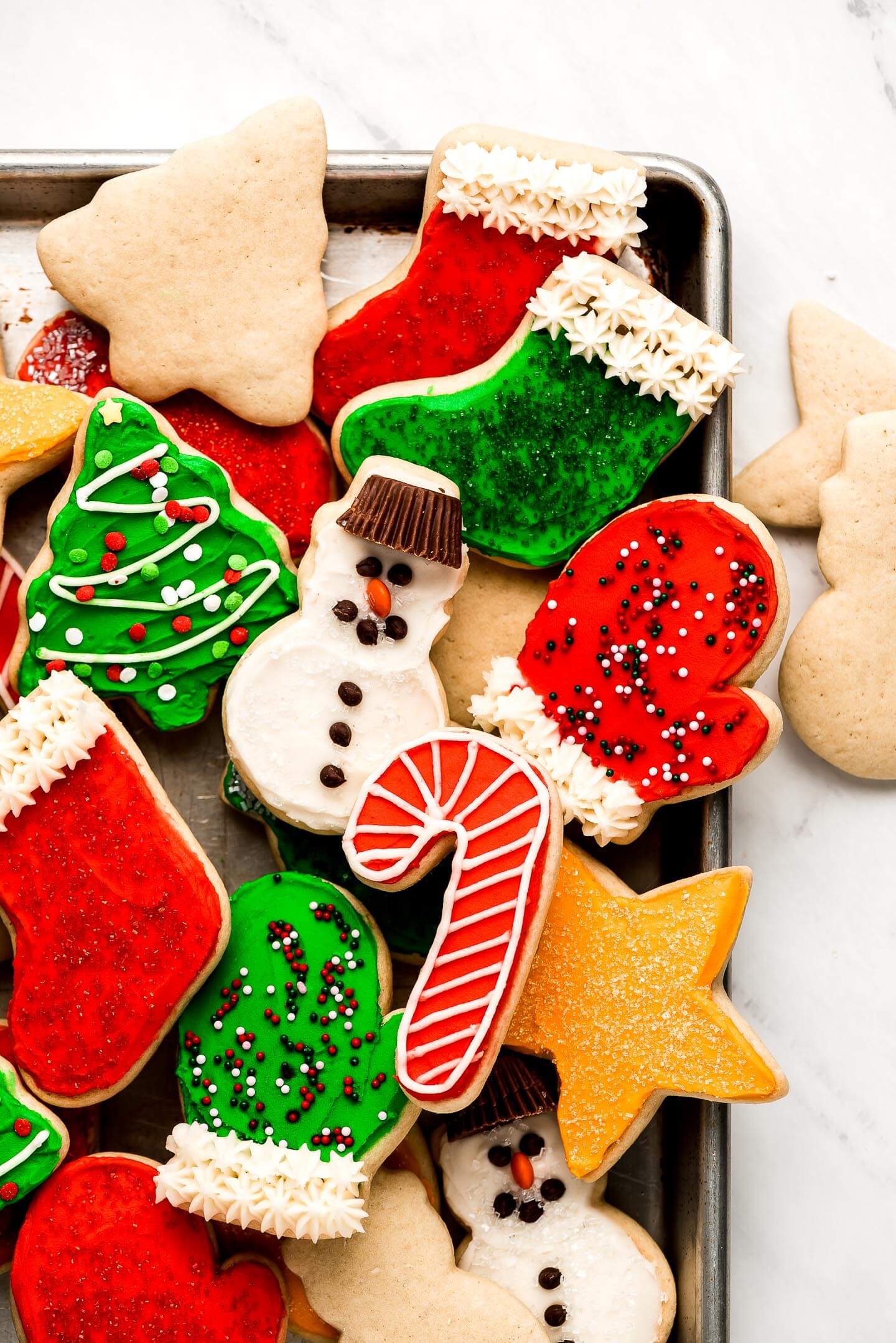 Many soft Sugar Cookies decorated for Christmas on a baking sheet.