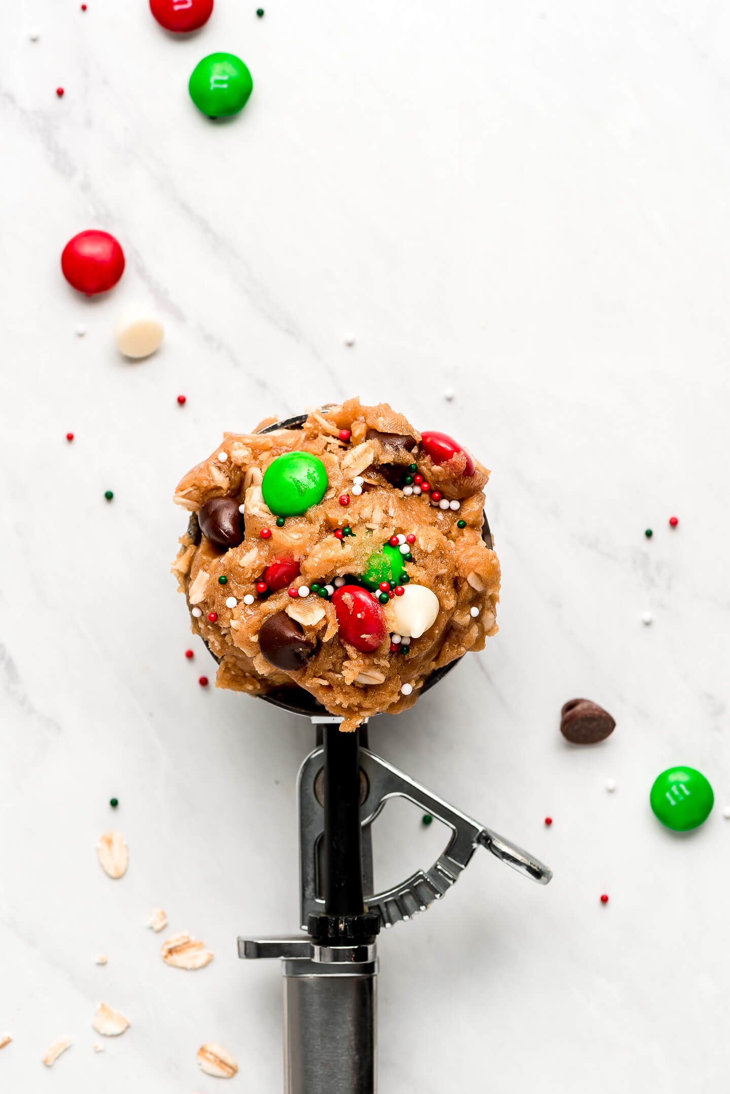 A trigger scoop full of cookie dough with red and green M&M's.