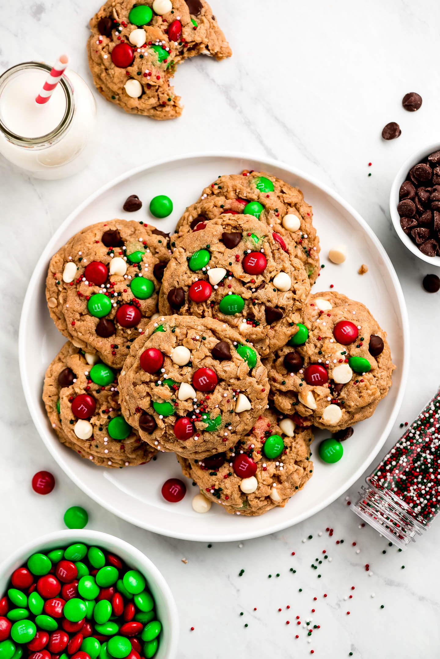 A plate full of Santa Cookies with bowls of chocolate chips, M&M's, sprinkles, and a jar of milk surrounding.