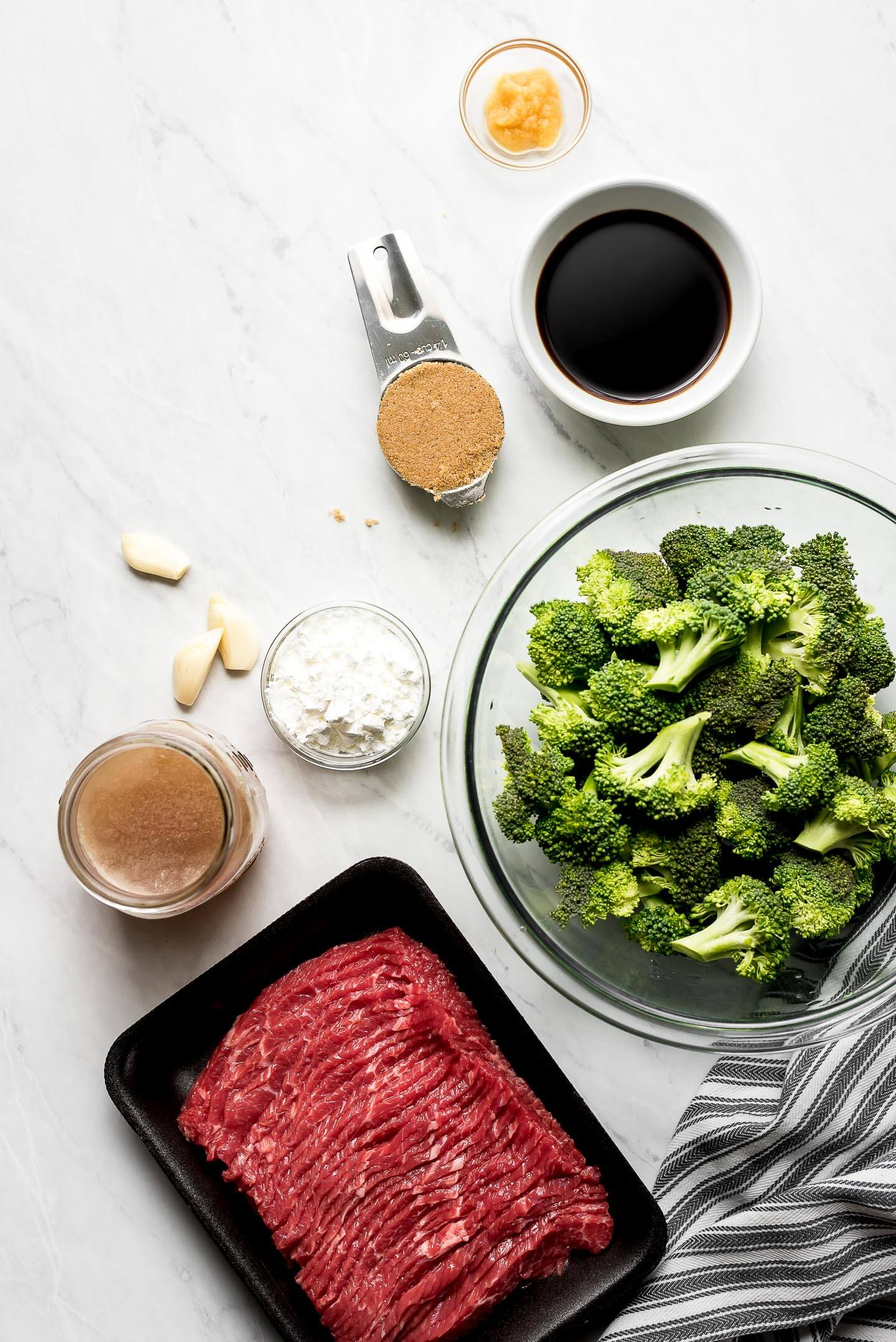 Ingredients on a marble surface- soy sauce, brown sugar, cornstarch, garlic, beef broth, broccoli, and thin cut flank steak.