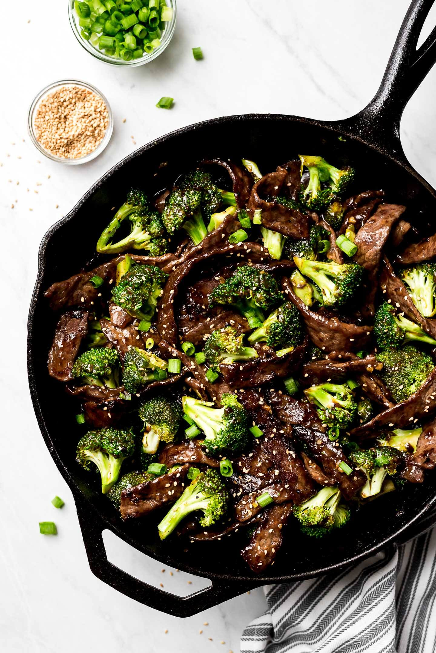 A skillet of Beef and Broccoli and small bowls of green onions and sesame seeds to the side.