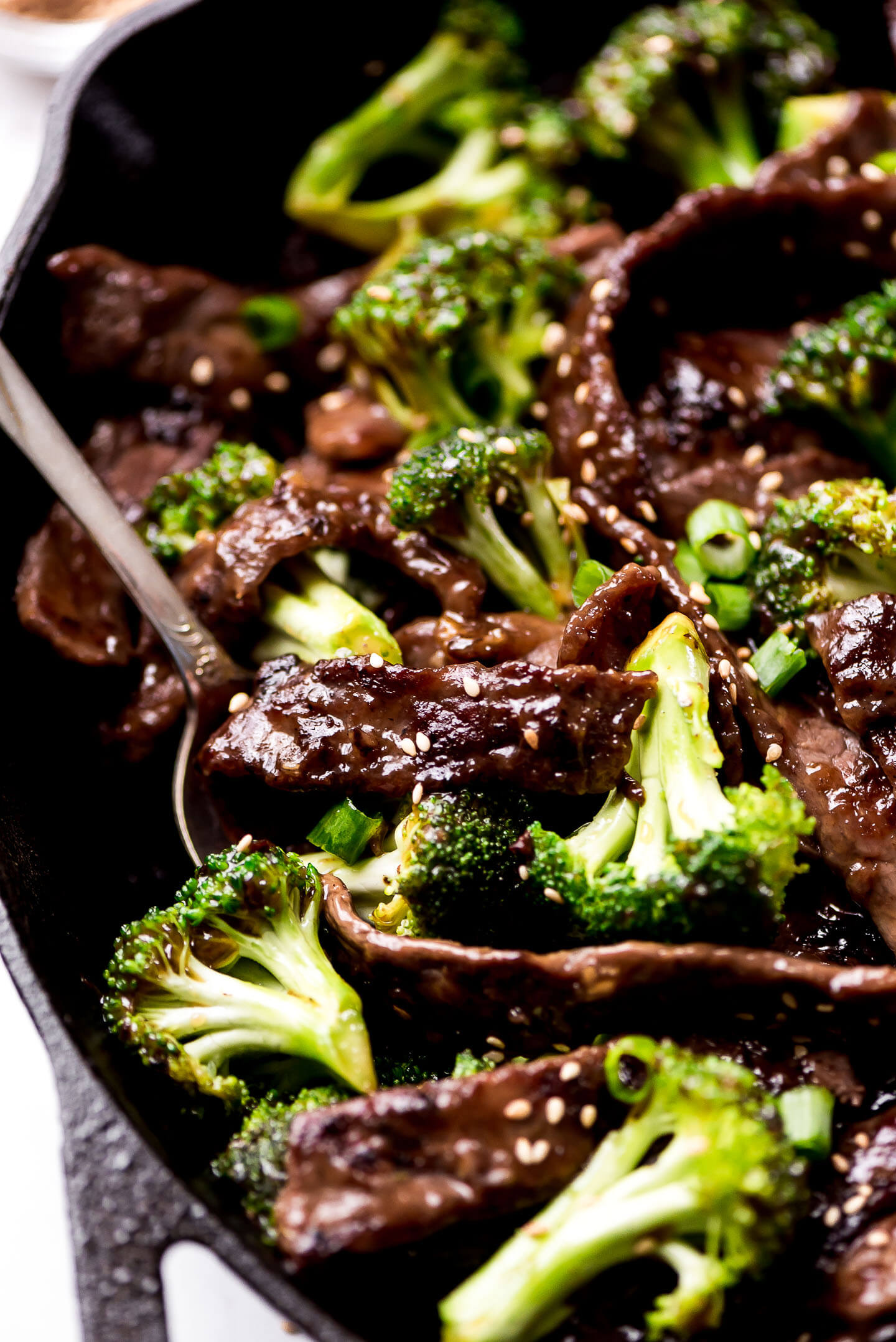 A close up shot of thin strips of Beef and Broccoli in a skillet.