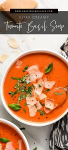 A bowl of Creamy Tomato Soup garnished with fresh basil and shaved parmesan.