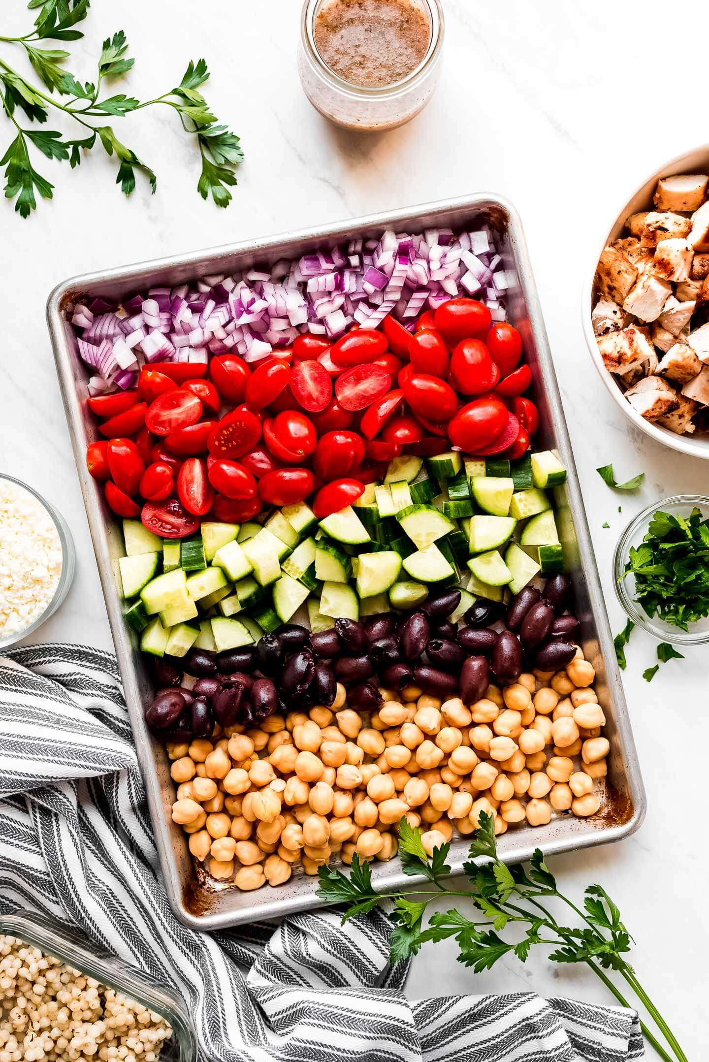A baking sheet with diced red onion, cherry tomatoes, cucumbers, Kalamata olives, and chickpeas.