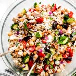 Greek Couscous Salad with chicken in a large mixing bowl with spoons.