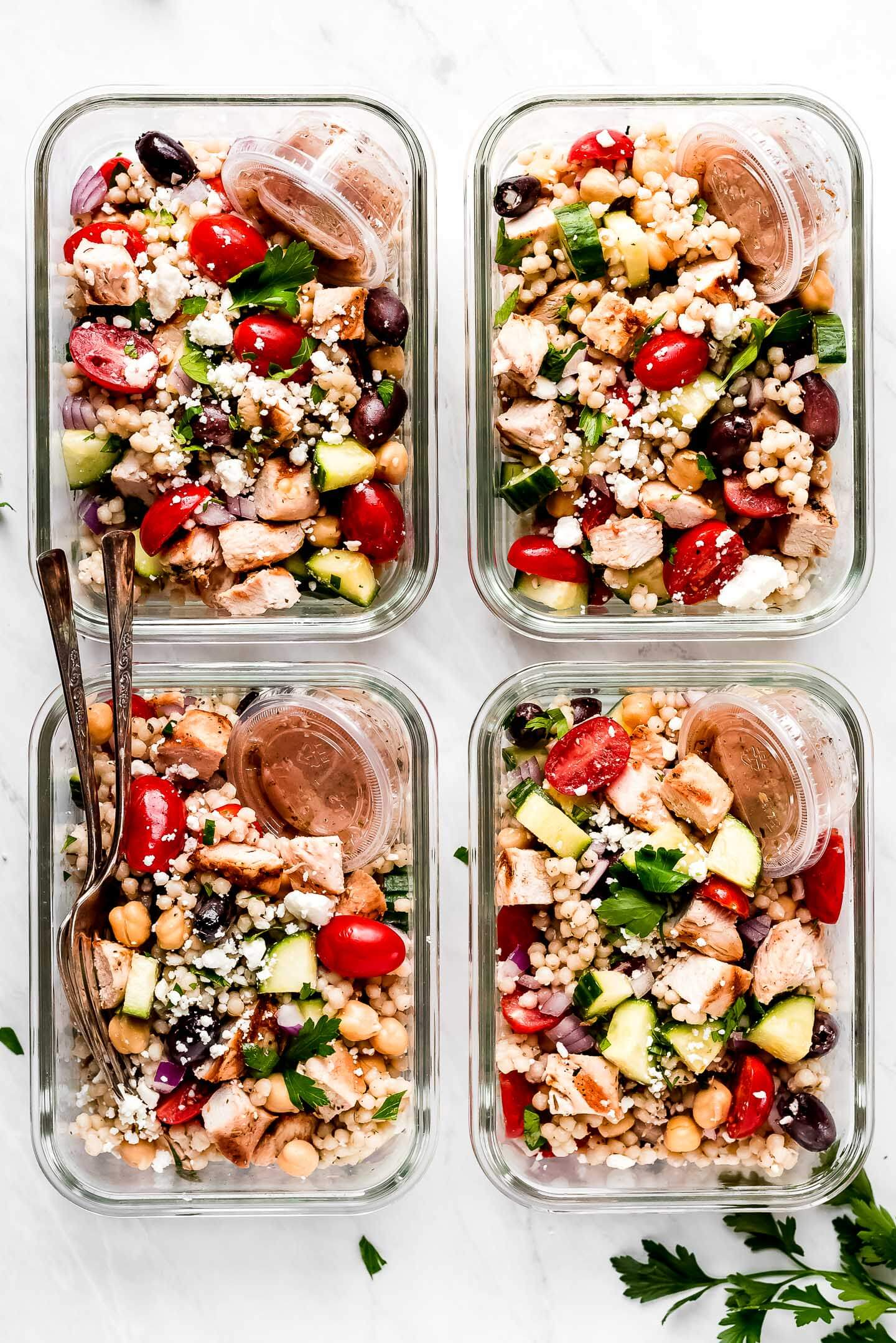 Four glass meal prep containers of chicken couscous salad.