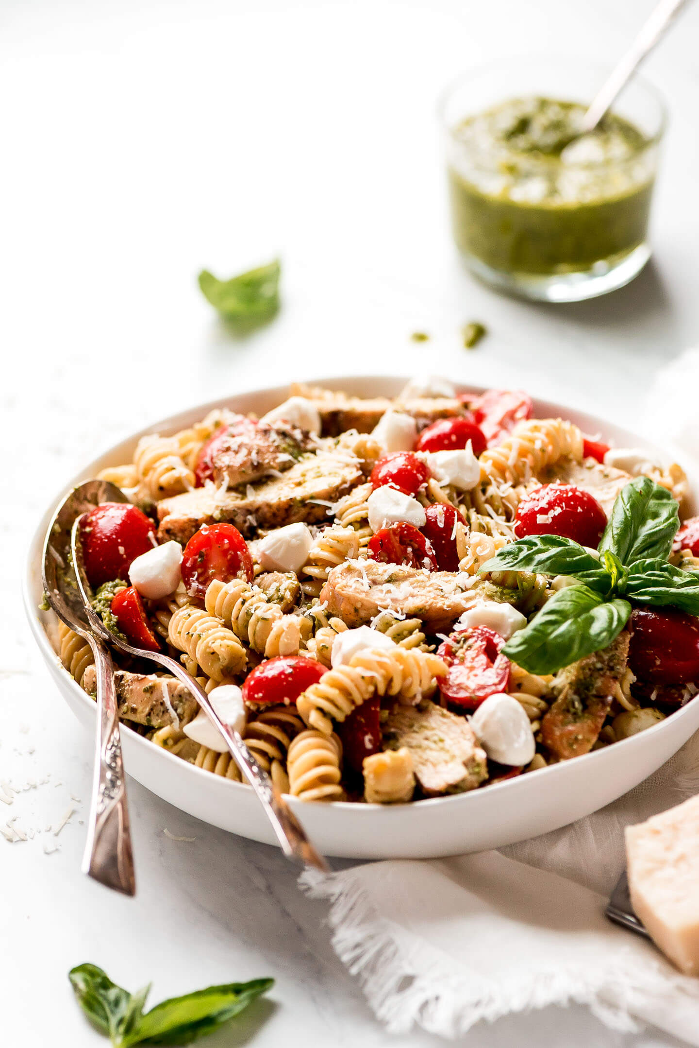 A serving bowl of pasta salad with chicken, tomatoes, mozzarella, and pesto.