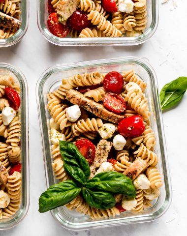 Multiple glass meal prep containers with Pesto Pasta Salad.