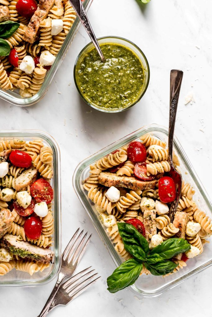 Meal prep pasta salad with chicken cheese, tomatoes, and pesto sauce.