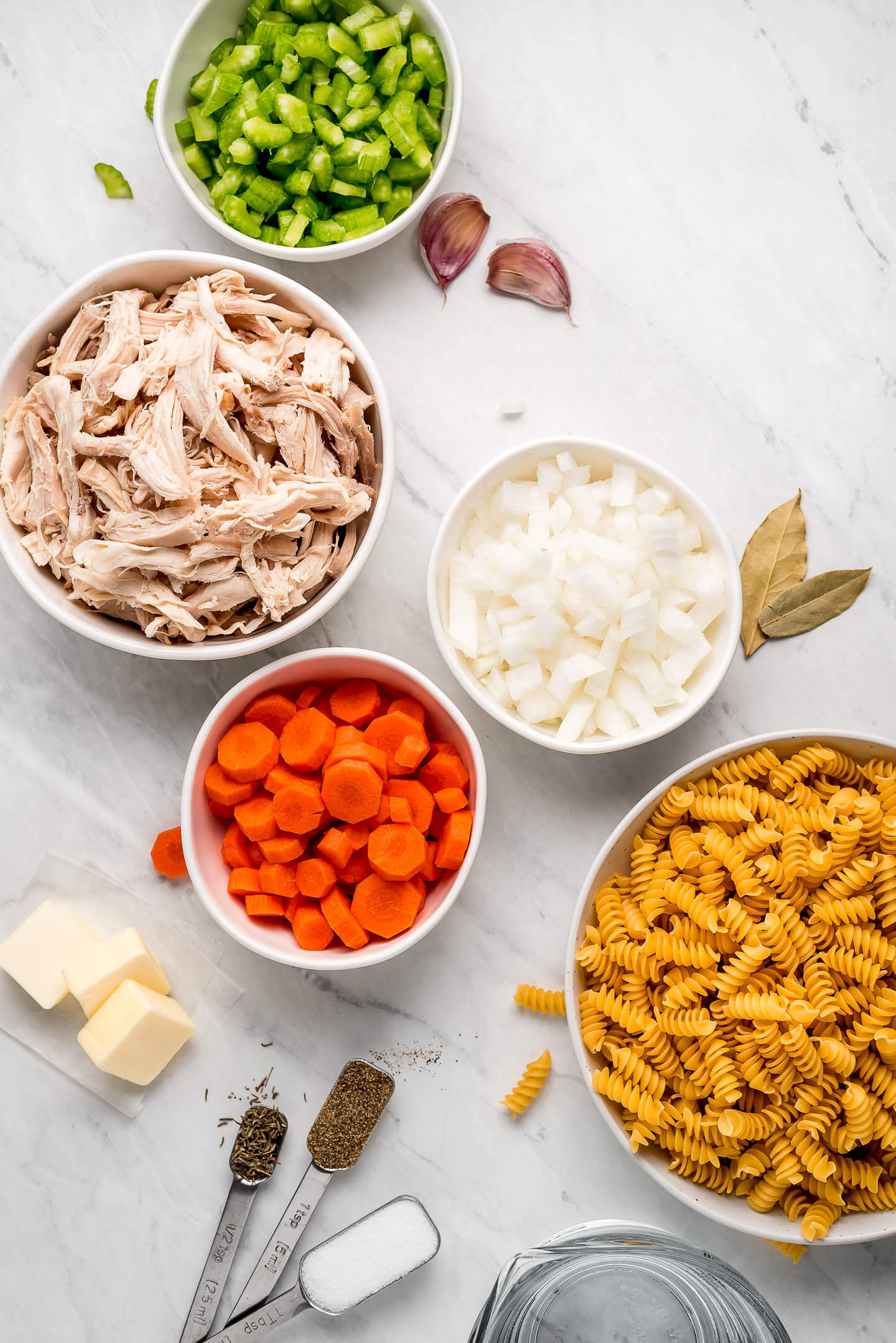 Ingredients on a marble surface- celery, shredded chicken carrots, onions, pasta, spices, butter.