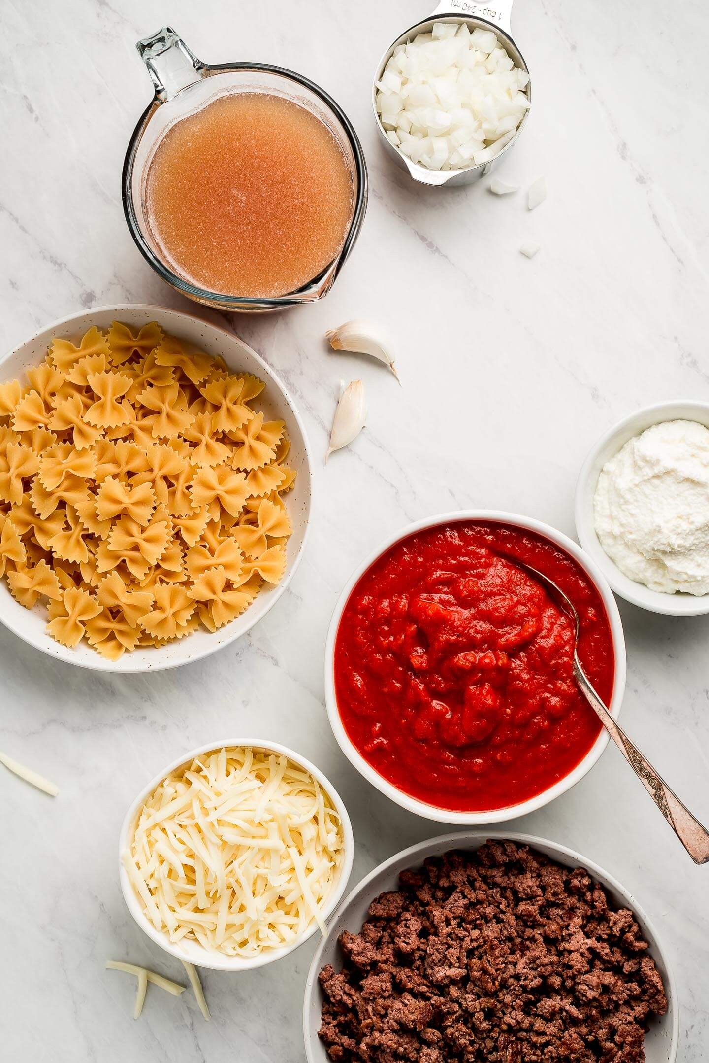 Ingredients on a marble surface in bowls-noodles, marinara sauce, ground beef, shredded cheese, broth, ricotta, onions.