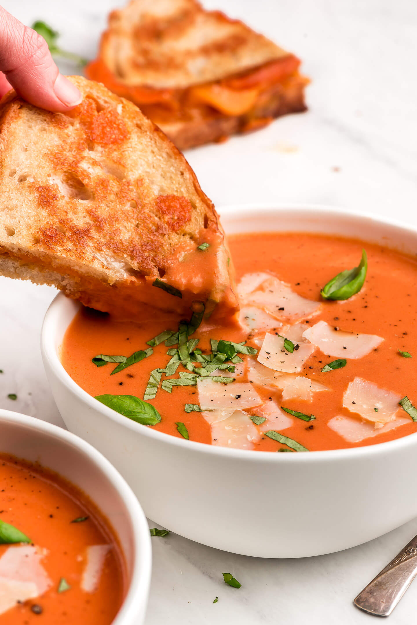 Dipping a grilled cheese sandwich into a bowl of Tomato Basil Soup.