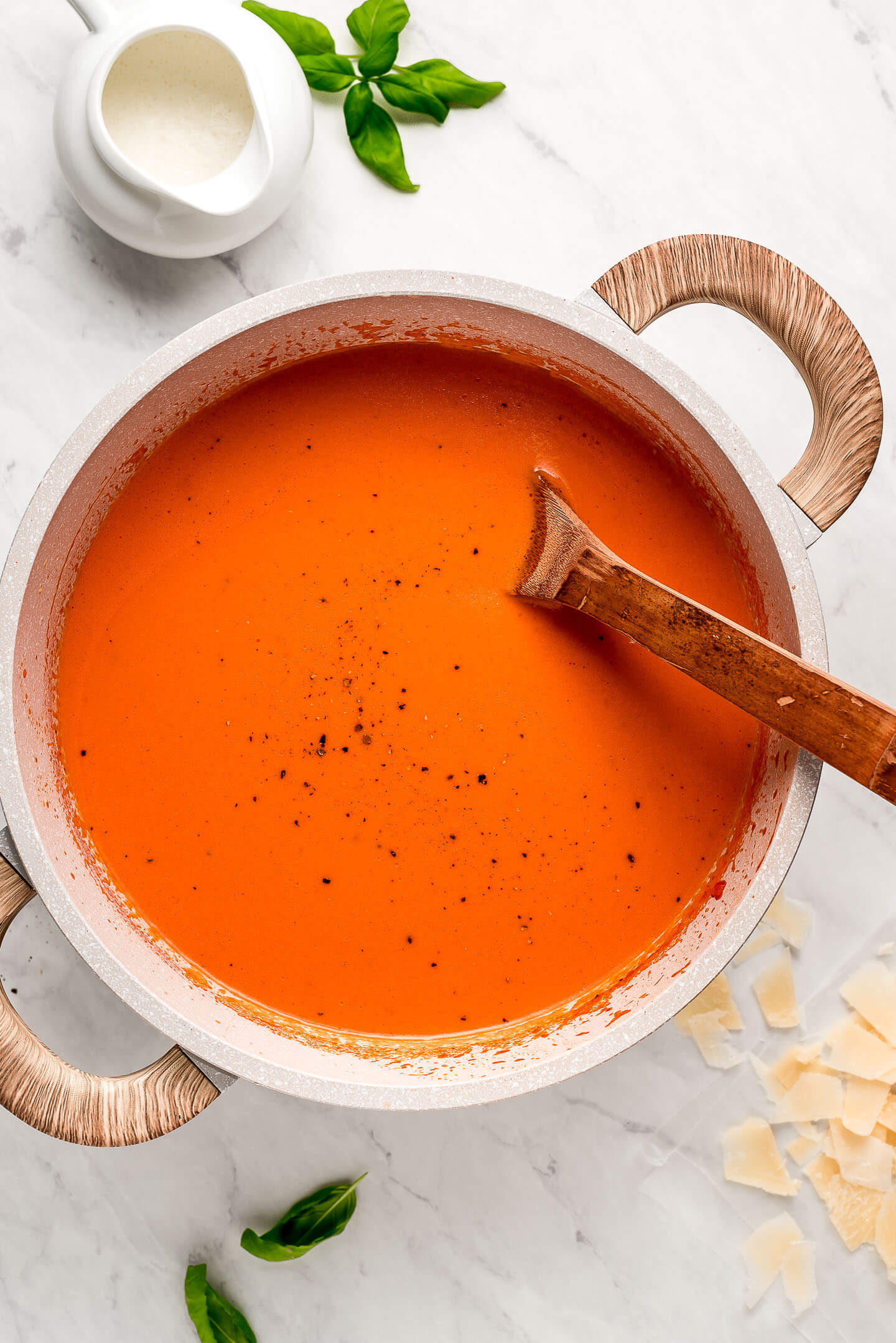 A large pot of Tomato Soup sprinkled with black pepper and parmesan and basil on the table.